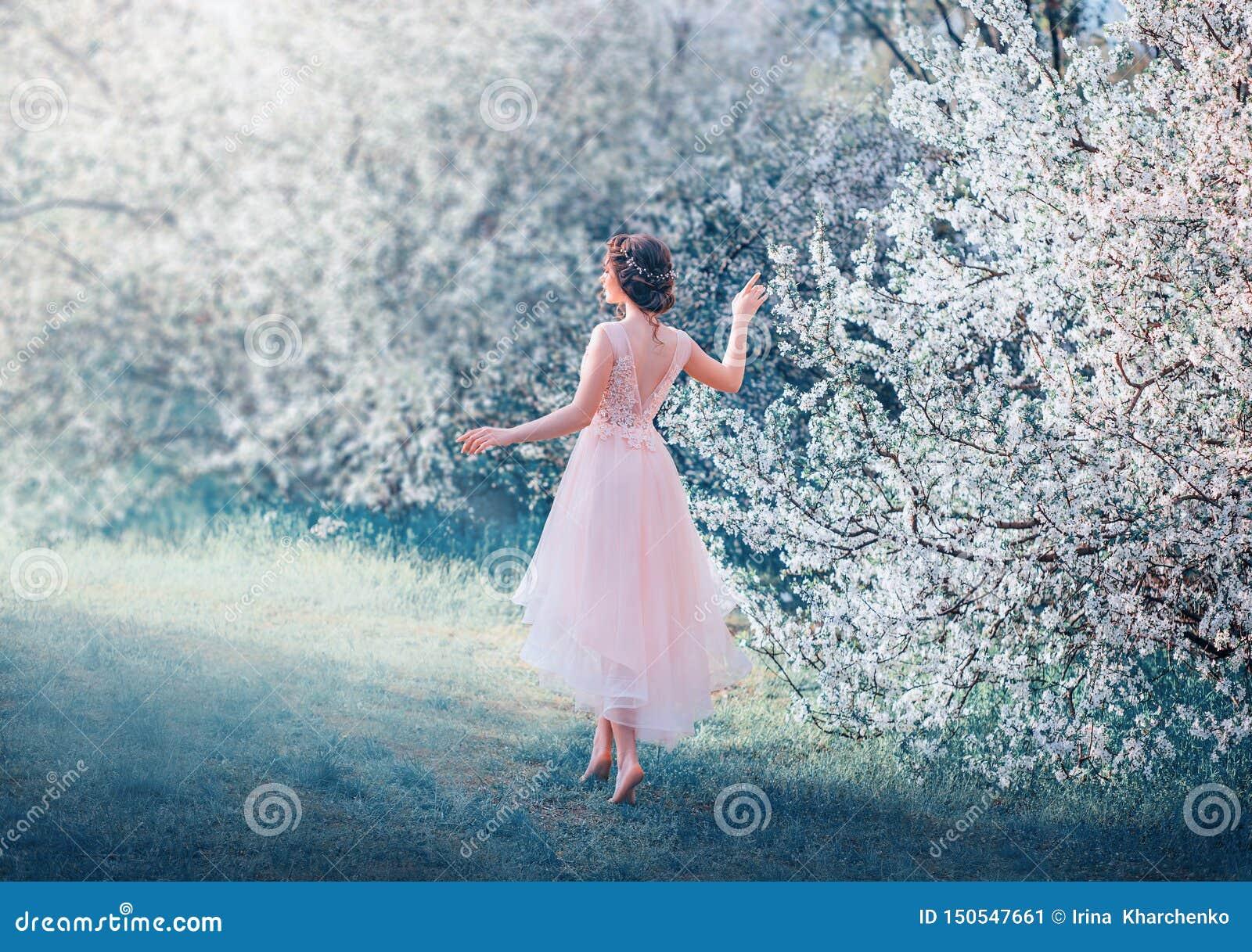 Den nätta spensliga flickan med flätat mörkt hår går, i att blomma trädgården barfota, prinsessan, går till solen, dam i delikat