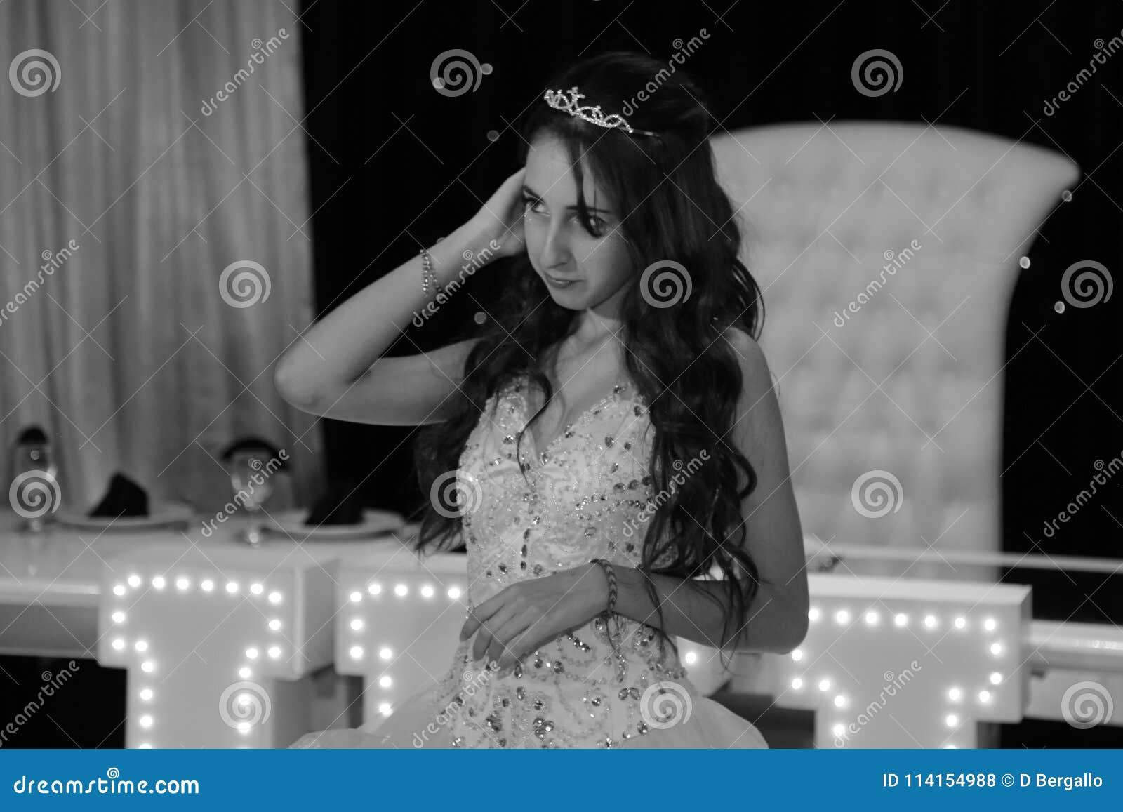 Den nätta tonåriga quinceanerafödelsedagflickan som firar i prinsessaklänningrosa färger, festar, special beröm av den passande k