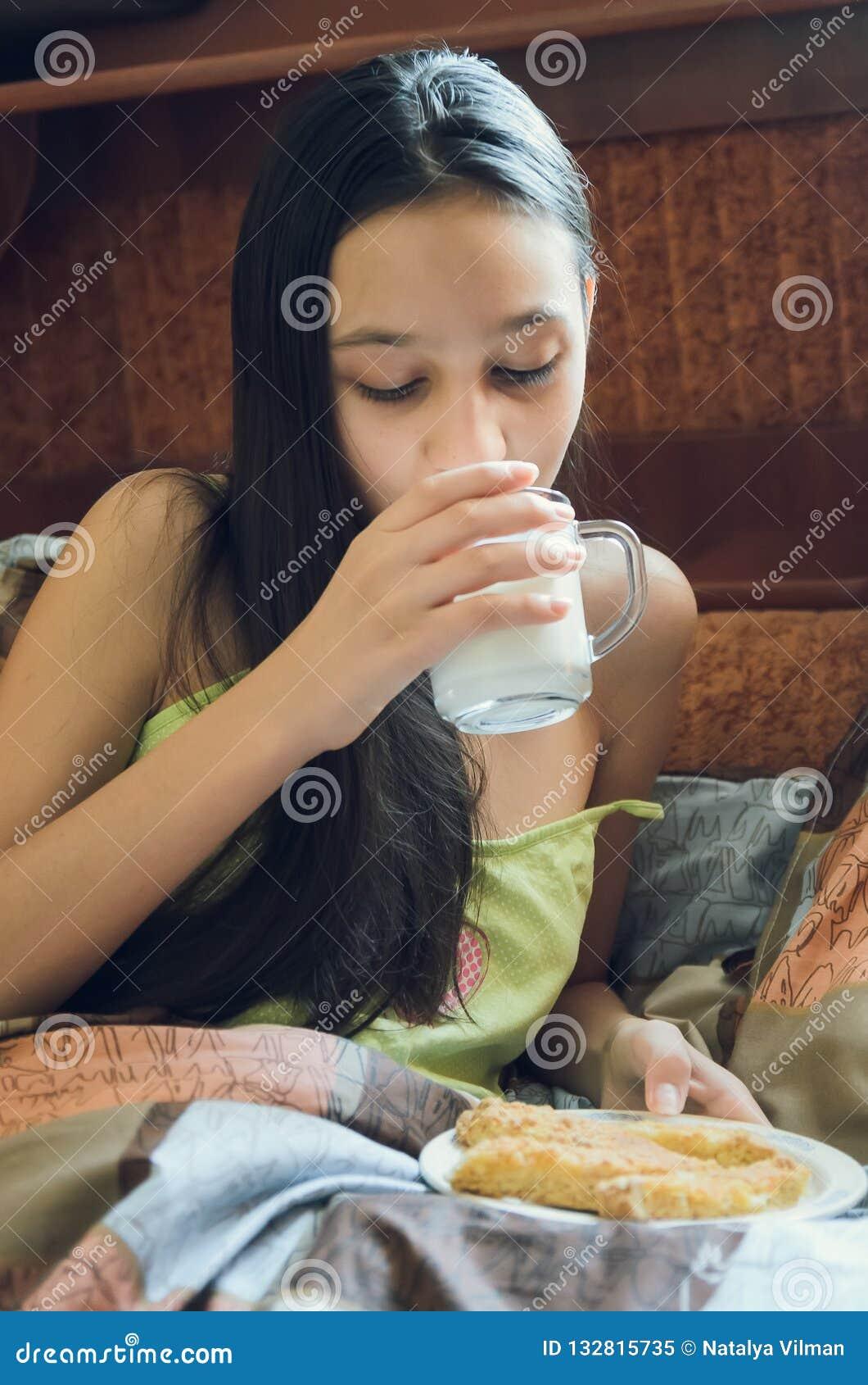 Den nätta unga brunetten som tycker om ett exponeringsglas av, mjölkar hemma och att le