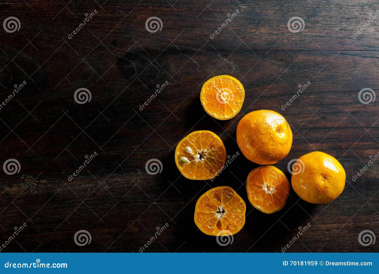 Den nya halvan klippte apelsiner på den mörka trätabellen