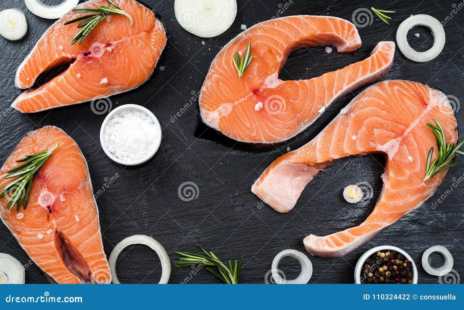 Den nya rå improviserade fisklaxen eller forellen, biffar, i en kastrull för att laga mat, med salt, pepprar på den svarta stenbe