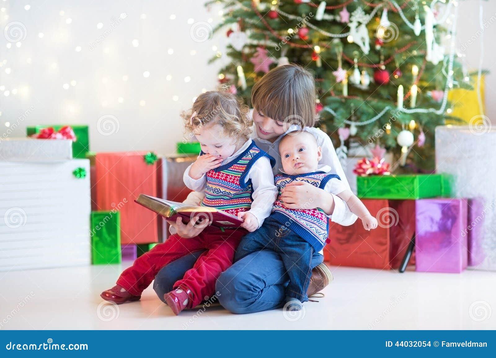 Den nyfödd gulliga lyckliga pojken som läser till hans litet barnsyster och, behandla som ett barn brodern i ett mörkt rum med ju