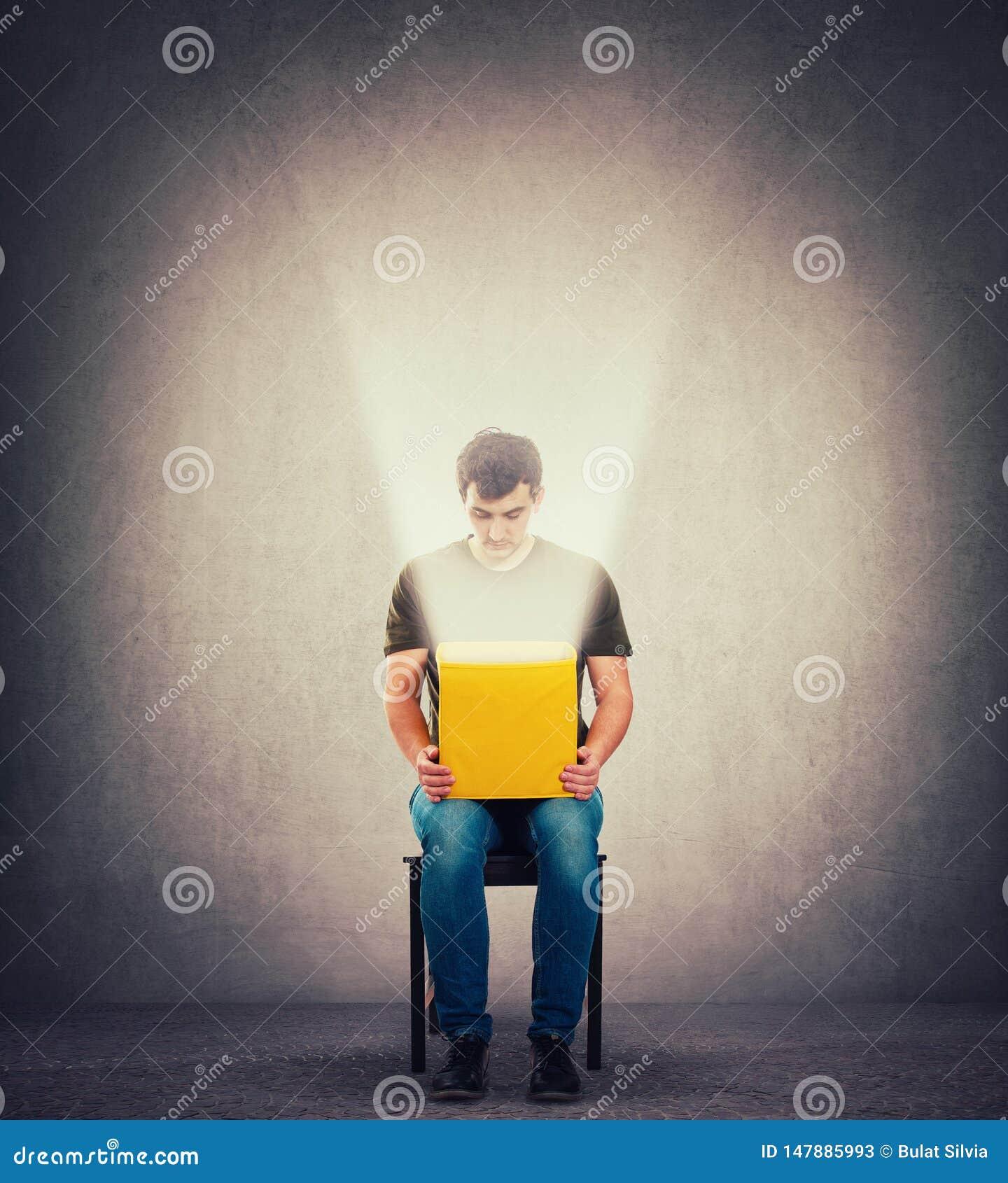 Den nyfikna mannen som sitter på en stol i ett mörkt rum som rymmer den gula asken på knä som inom ser som ett magiskt ljus, komm