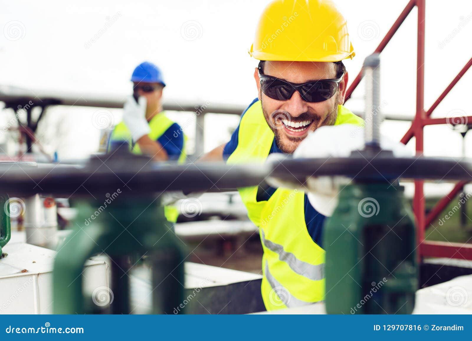 Den olje- arbetaren stänger ventilen på den olje- rörledningen