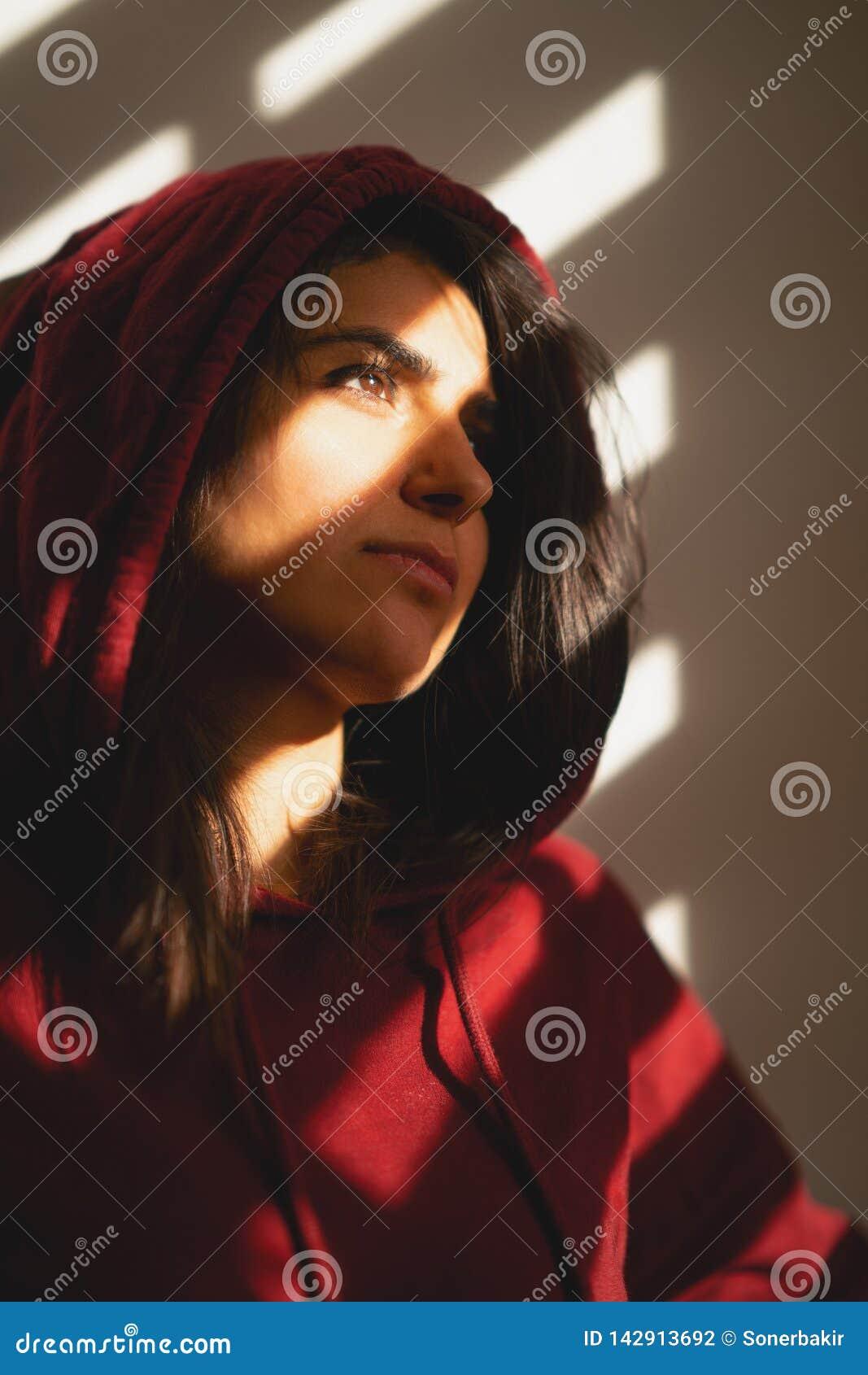 Den olyckliga flickan står bara på fönsterrullgardinerna