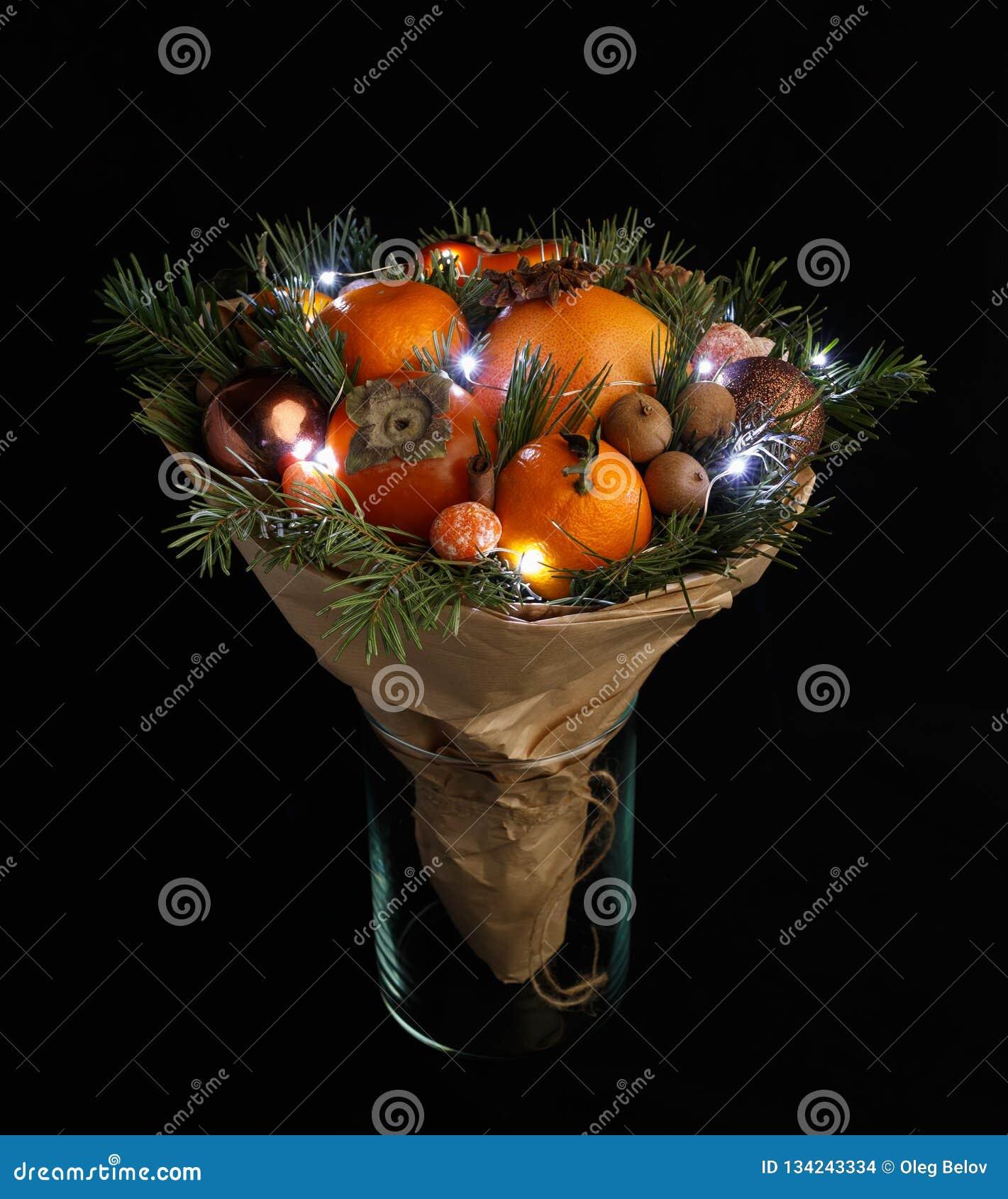 Den original- julbuketten som består av persimonet, mandariner, muttrar, kanelpinnar och, sörjer ris som slås in i kraft papper o