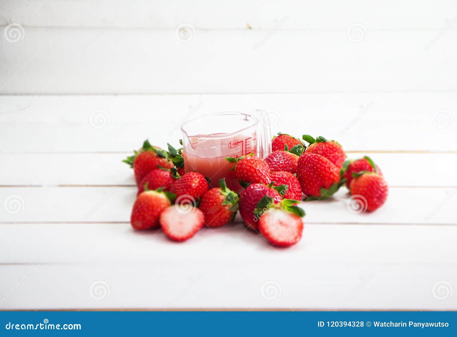 Den oskarpa ljusa designbakgrunden av jordgubbefruktsaft i plast- kopp