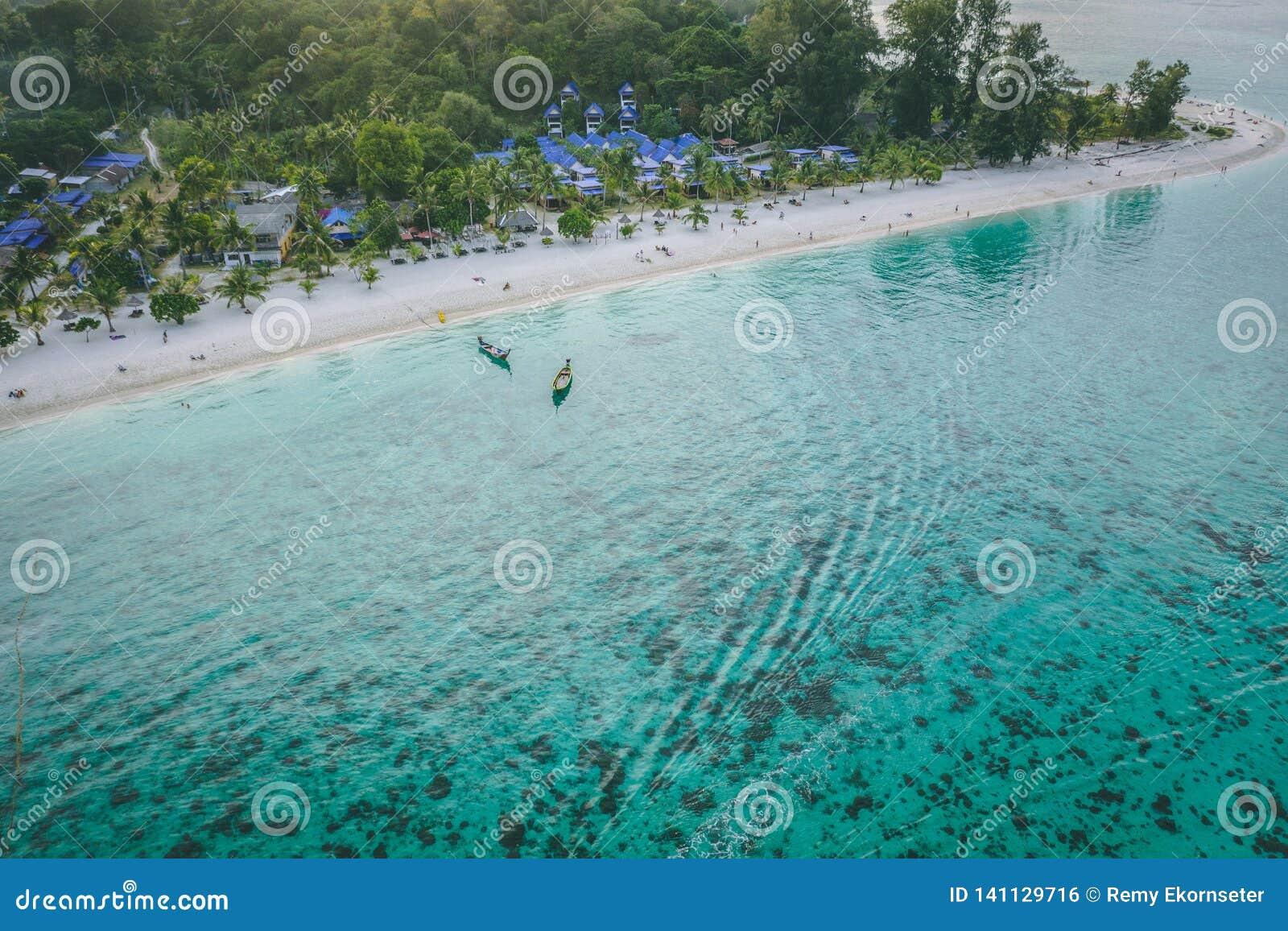 Den Paradise ön Crystal Clear Sea som är blå, gömma i handflatan, på fyre