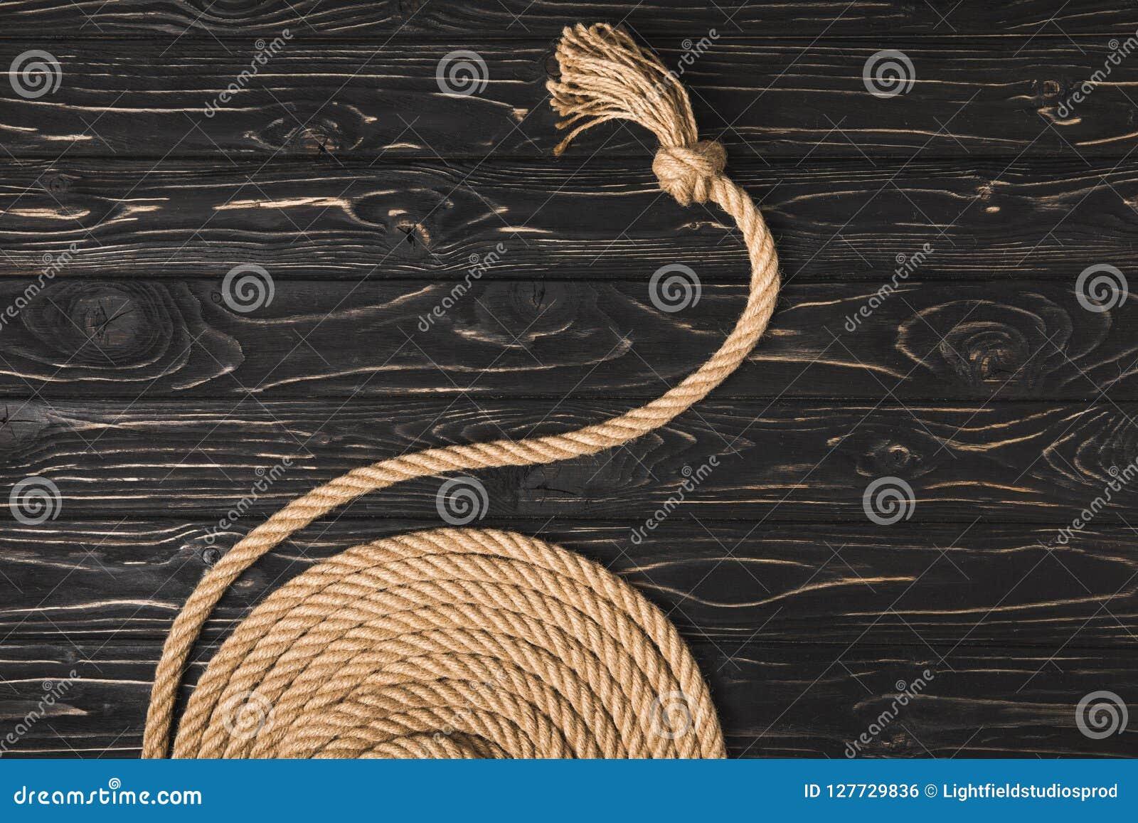 Den partiska sikten av brunt knöt det nautiska repet som var ordnat i cirkel på träyttersida