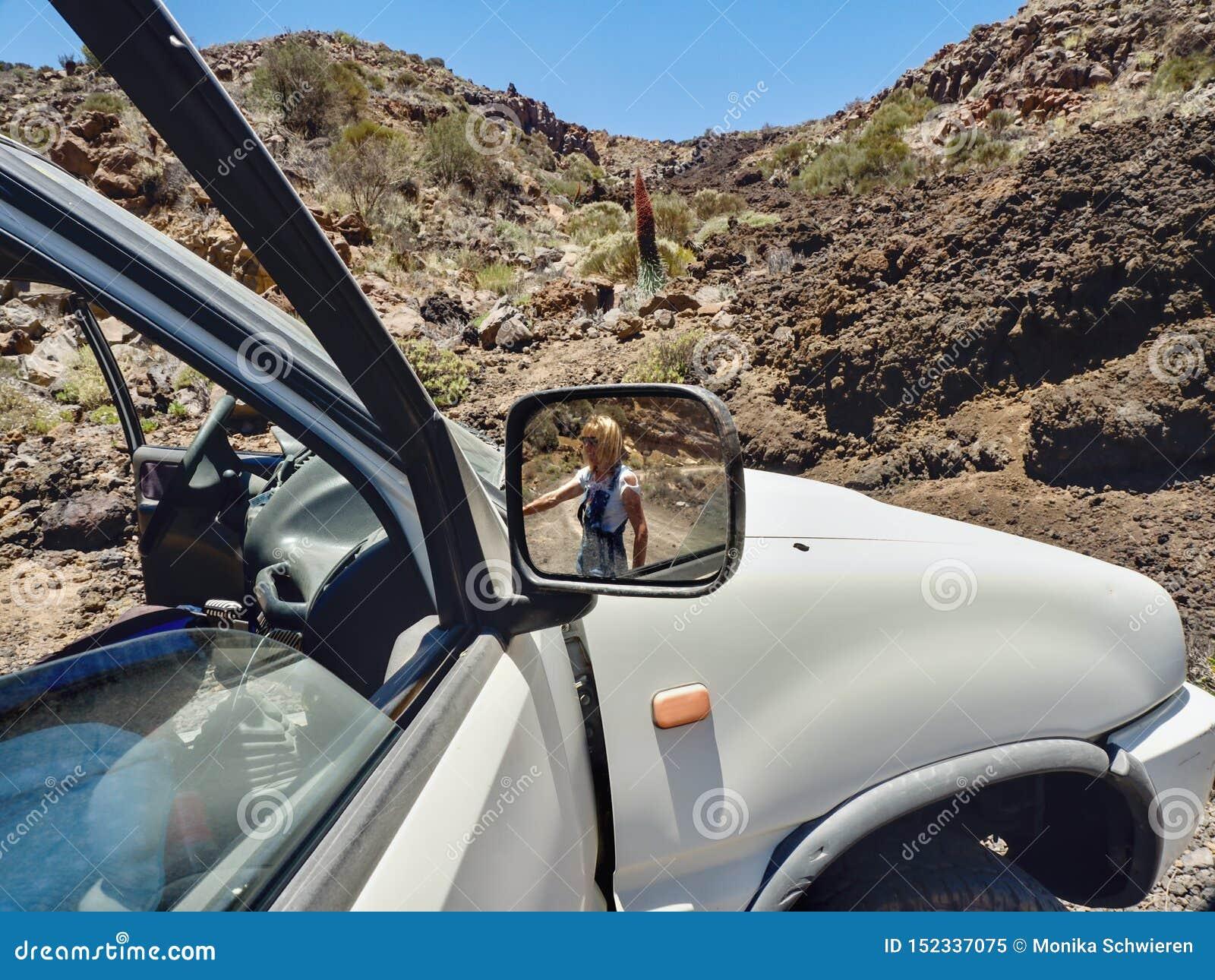 Den partiska sikten av en stor bil, i rätsidaspegeln är en kvinna som ser i bakgrunden den karga öknen