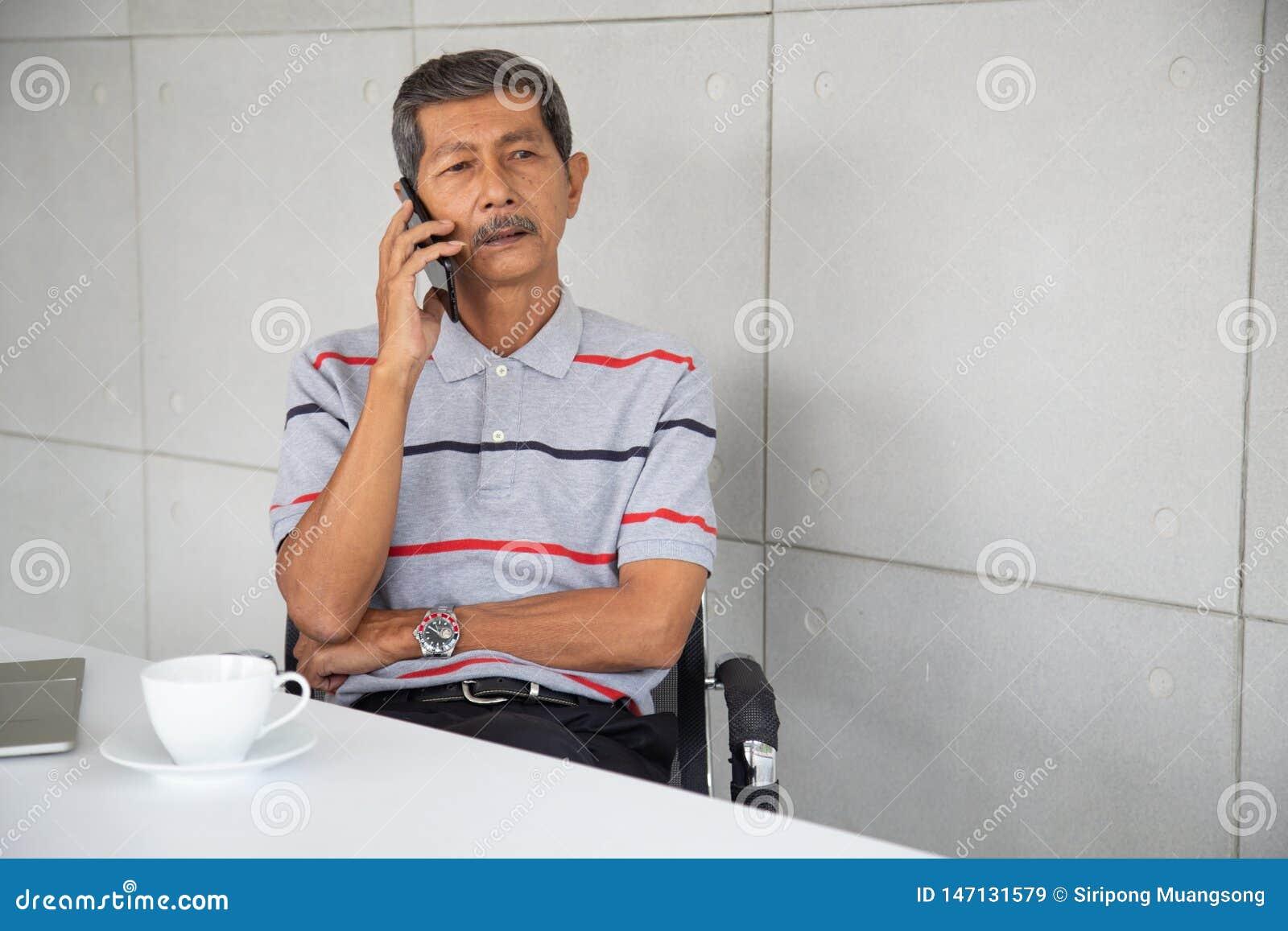 Den pensionärAsien affärsmannen sitter och osemobiltelefonen