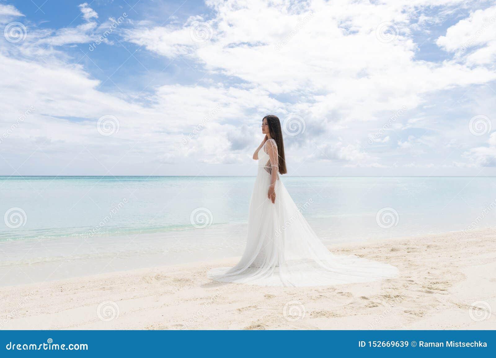 Den perfekta bruden En ung brud i en vit klänning står på en snövit strand