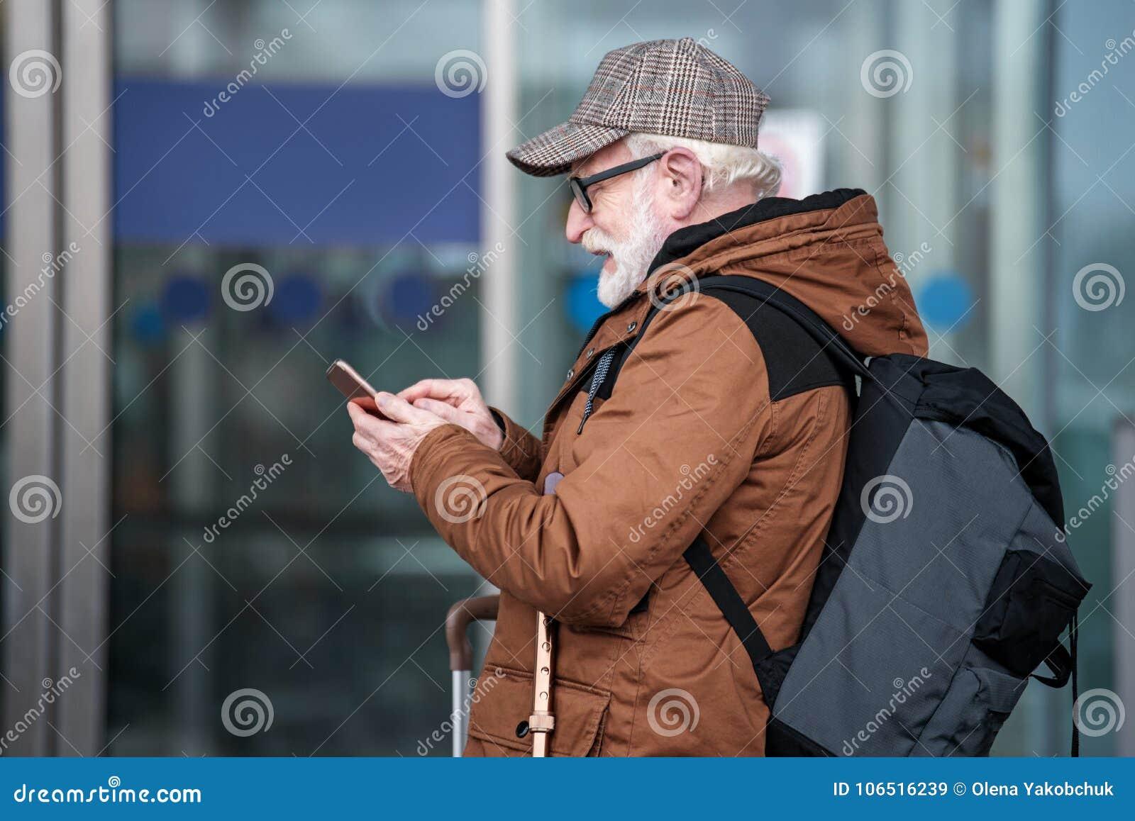 Den positiva gråhåriga mannen är den hållande smartphonen