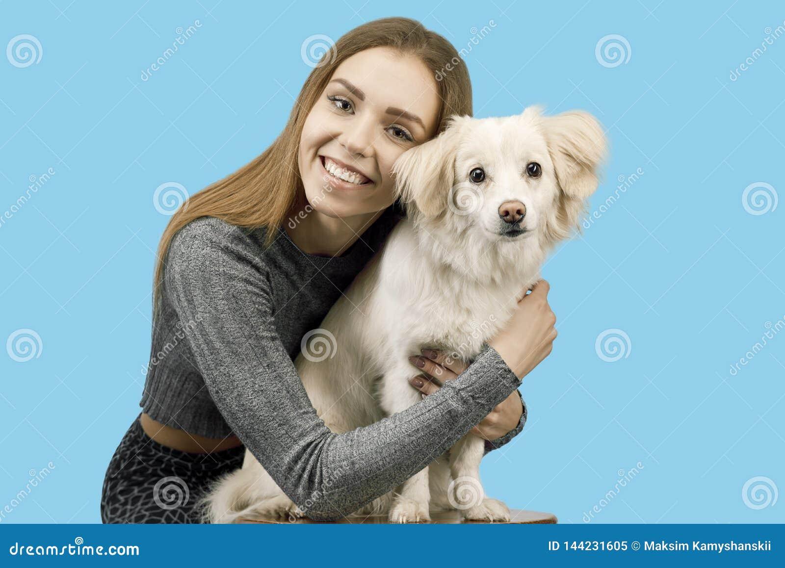 Den positiva kvinnlign med glat uttryck och hennes hund som tillfredsställs efter, går utomhus-, har bra förhållanden