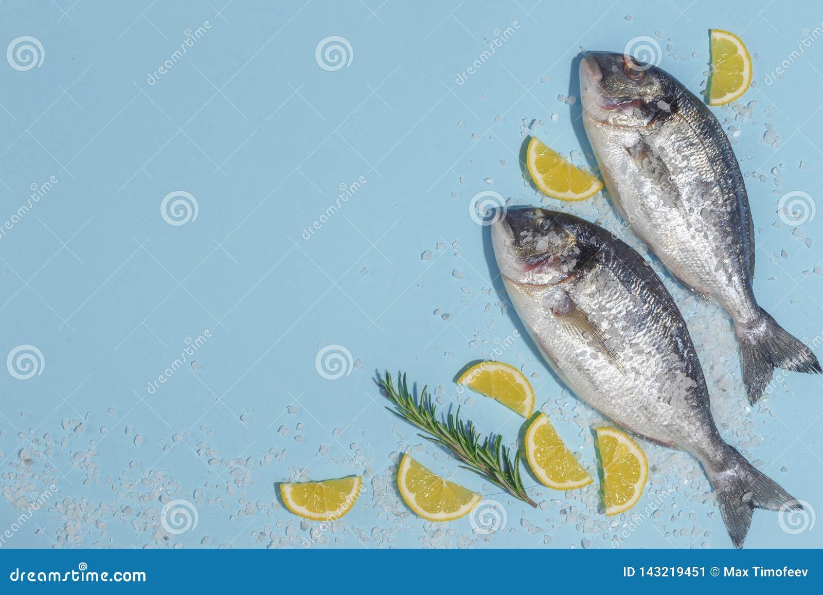 Den rå doradafisken med kryddor, saltar, citronen och örter, rosmarin på enblått bakgrund Top beskådar