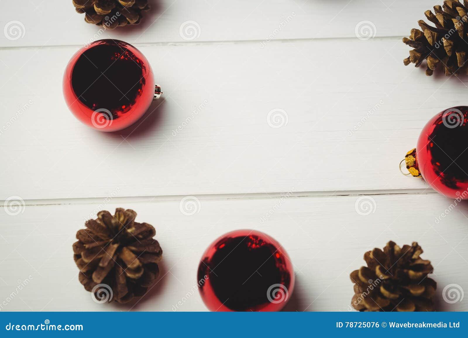 Den röda julstruntsaken och sörjer kotten på trätabellen