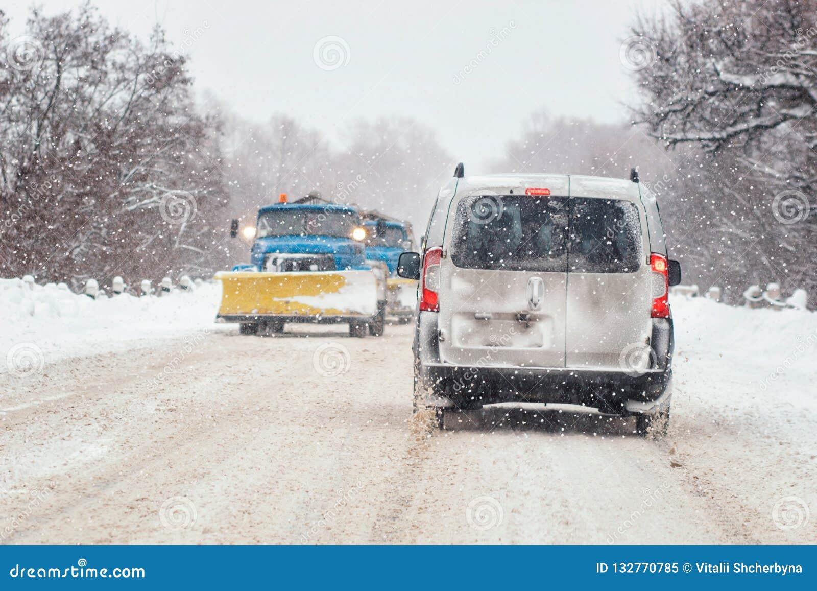 Den rörande bilen på den snöig vintervägen bland djupfryst skog efter regnar snöslask Kallt väder, snöstorm, dålig synlighet, hal
