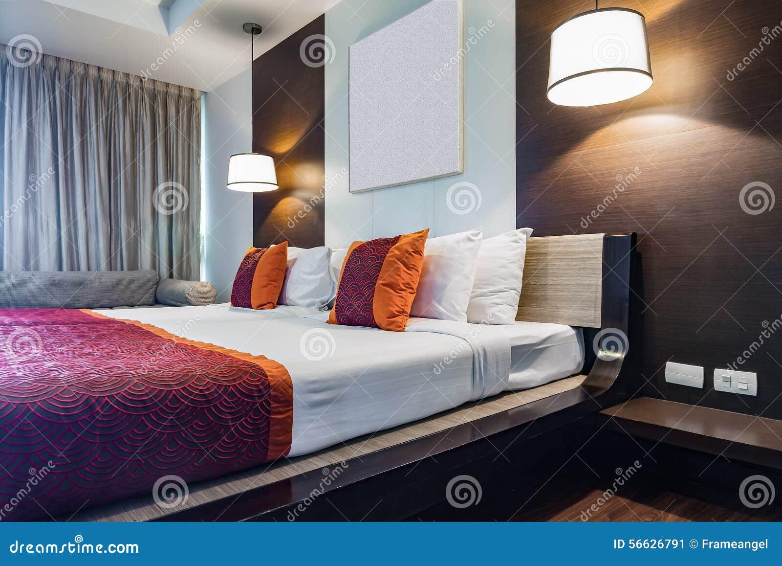 Den röda kudden på dubbelt sovrum med den vita bedsheeten och ...