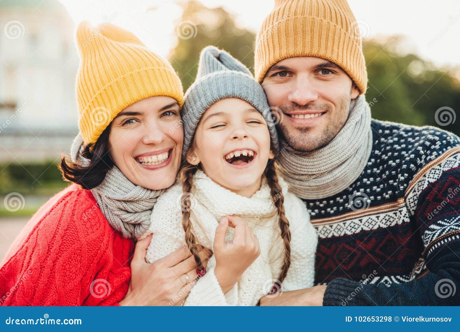 Den roliga extatiska lilla ungen skrattar, som har underbar tid med henne föräldrar Tillgivna föräldrar står nära deras lilla dot