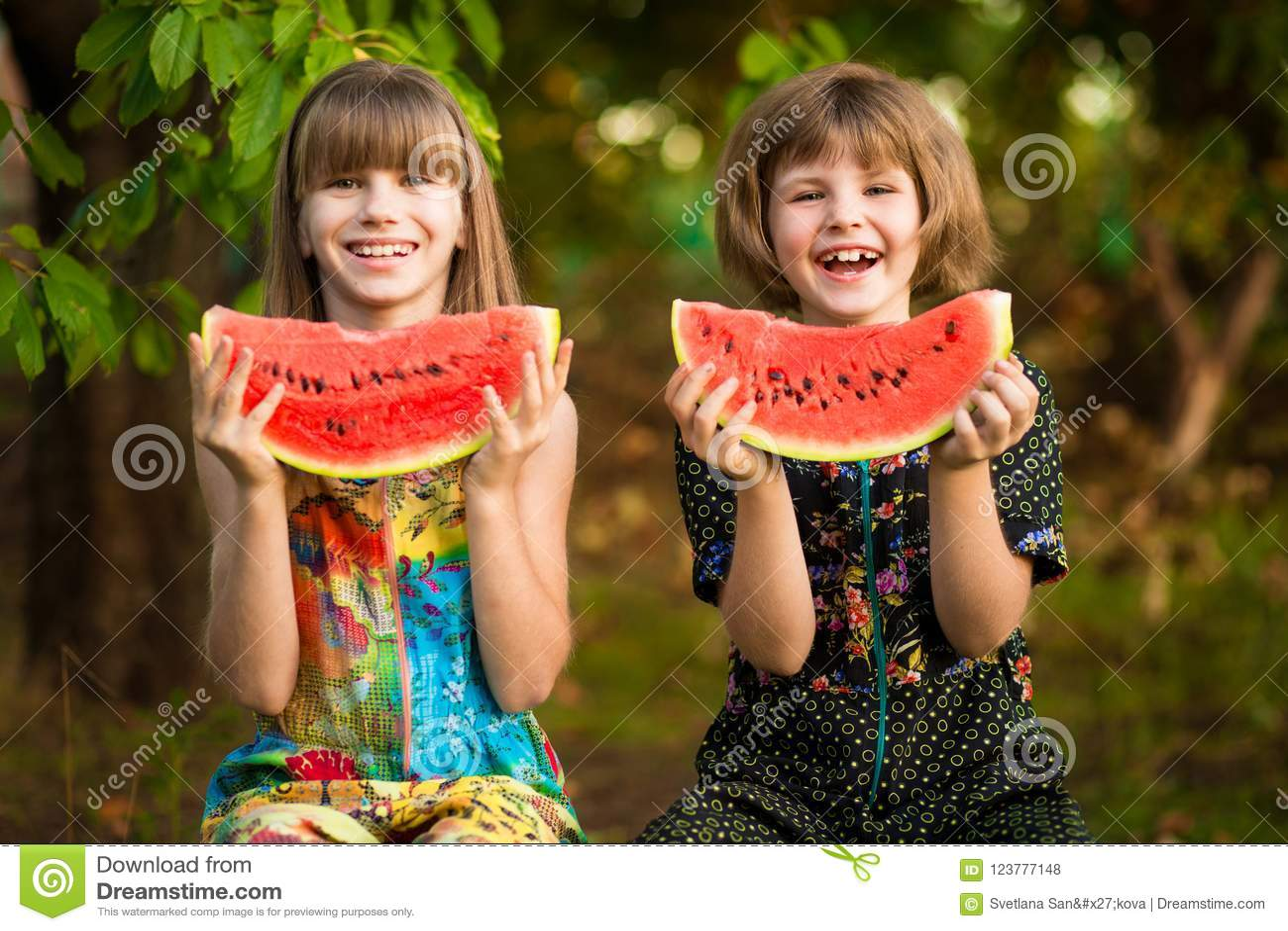 Den roliga flickan för små systrar äter vattenmelon i sommar