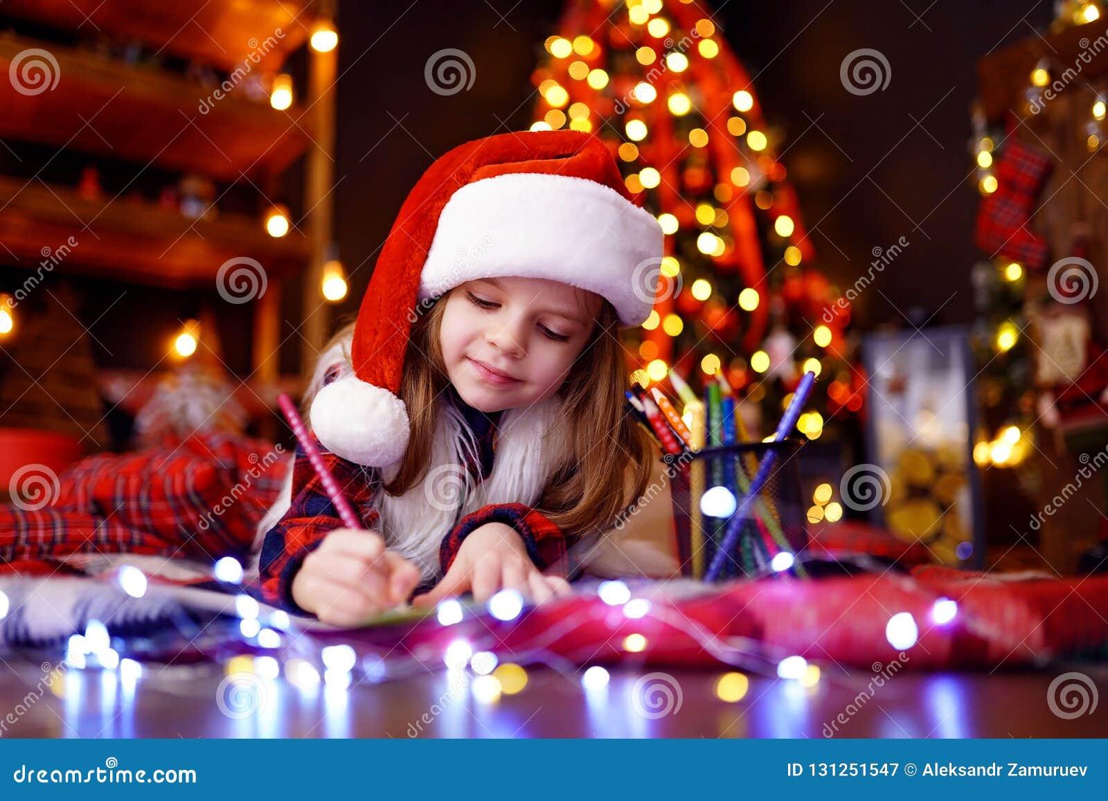 Den roliga flickan i den Santa hatten skriver bokstaven till Santa
