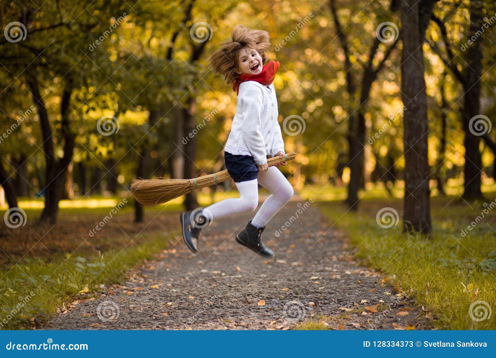 Den roliga lilla flickan flyger på kvasten i höst