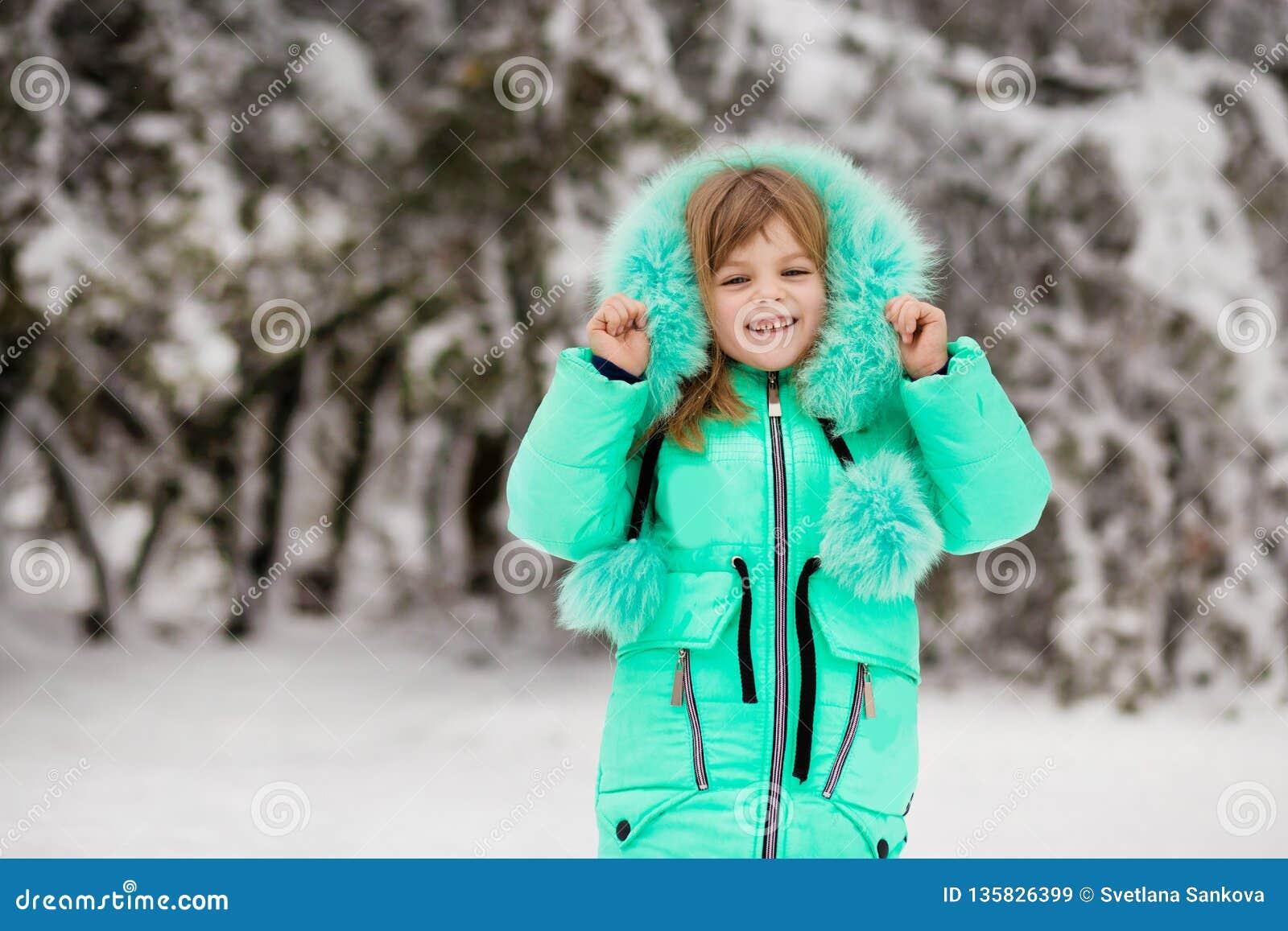 Den roliga lilla flickan som har gyckel i härlig vinter, parkerar