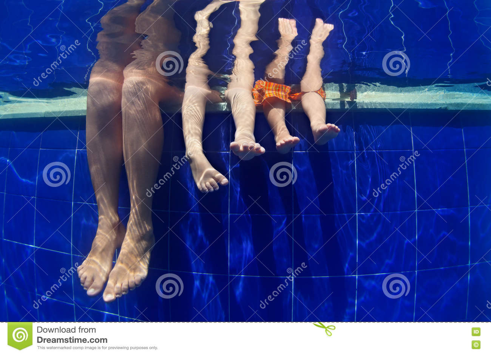 Den roliga undervattens- fotomodern med ungar lägger benen på ryggen i simbassäng
