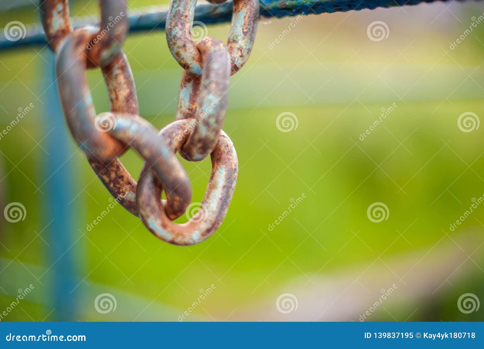 Den rostiga kedjan hänger på ett blått staket i eftermiddagen
