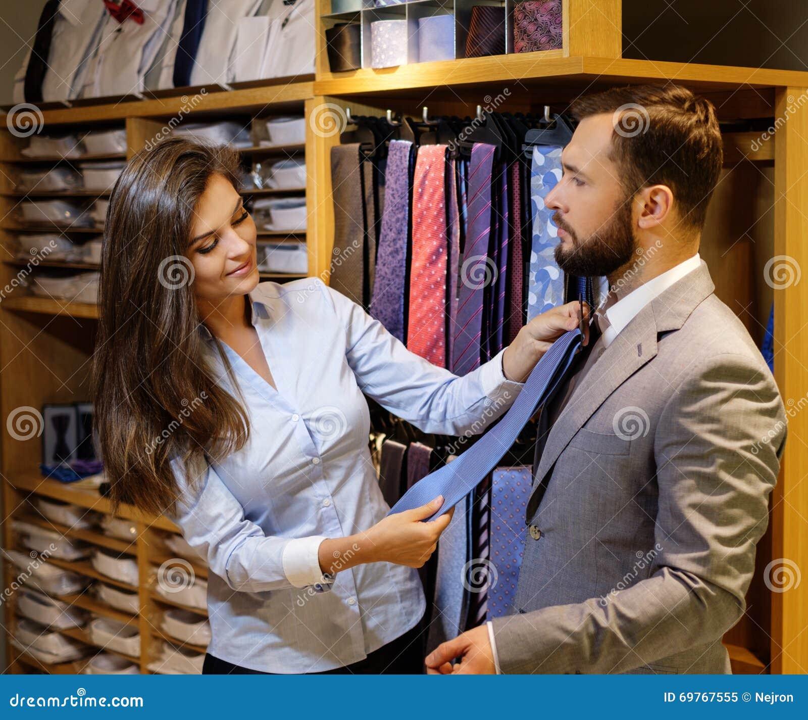 Den säkra stiliga mannen med skägget som väljer ett band i en dräkt, shoppar