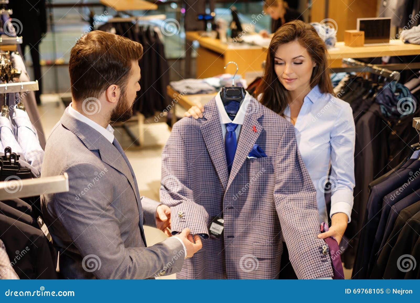 Den säkra stiliga mannen med skägget som väljer ett omslag i en dräkt, shoppar