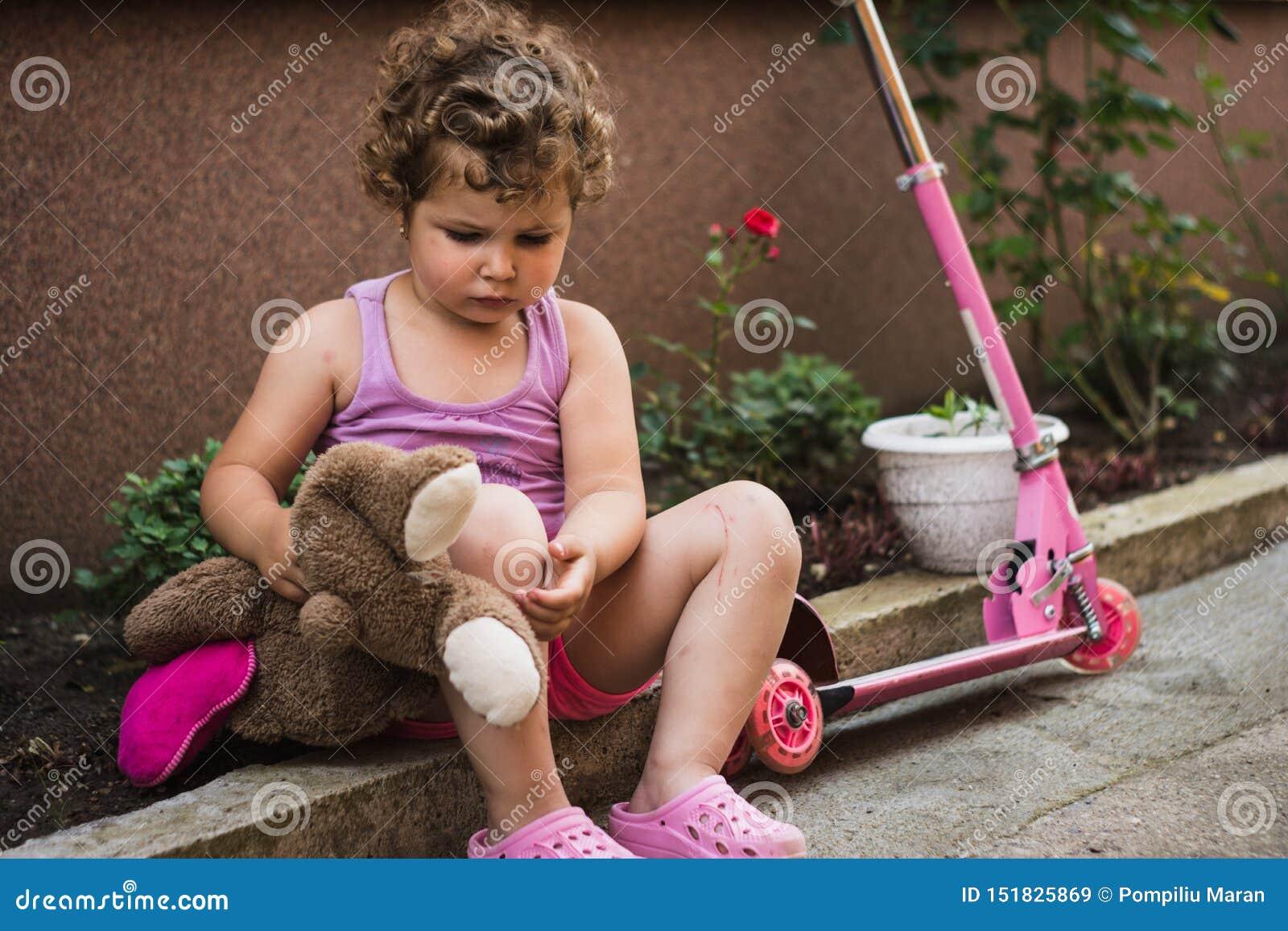 Den söta lilla flickan med lockigt hår är sitta och vila nära hennes rosa sparkcykel i borggården