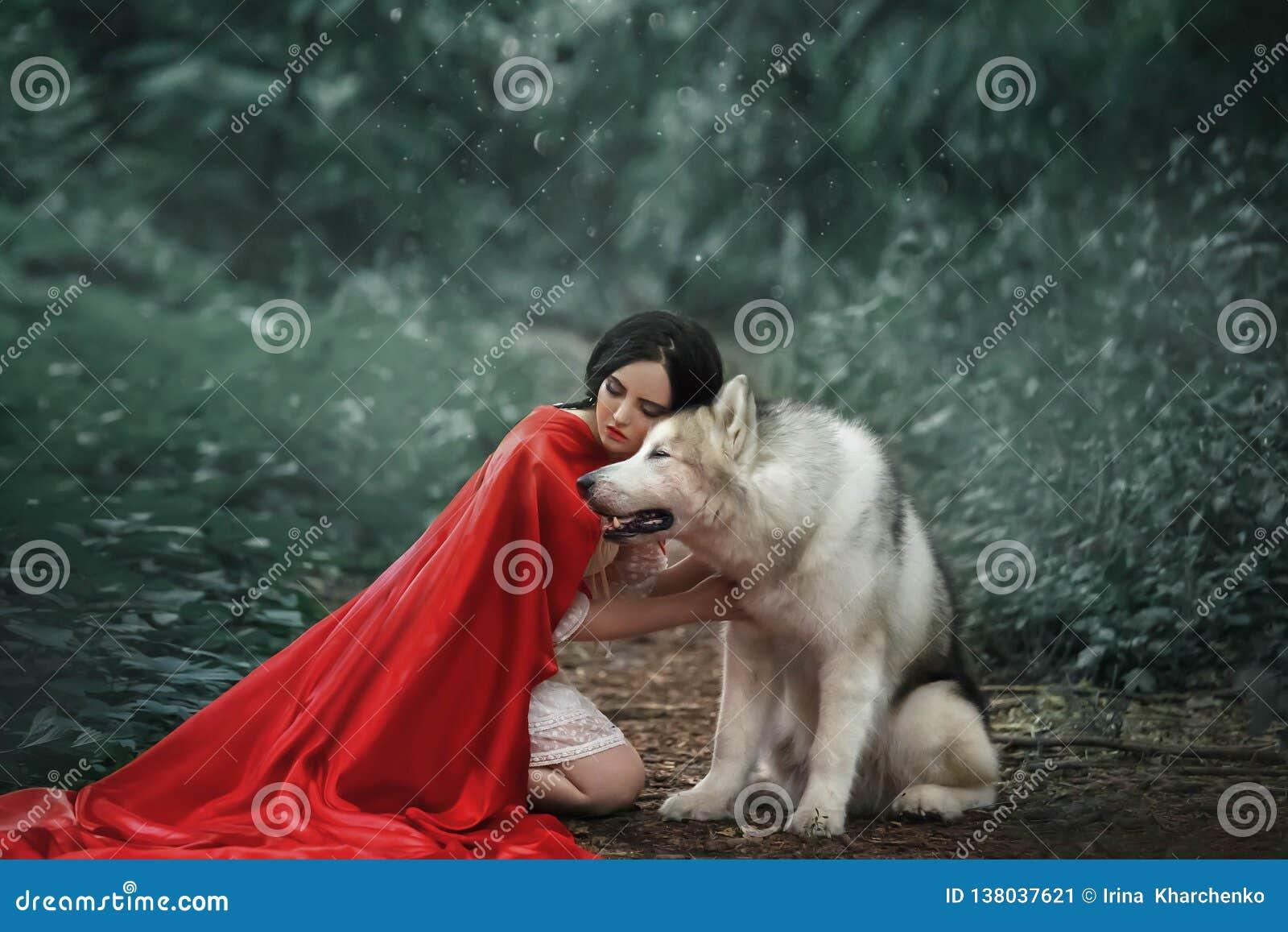 Den sagolika bilden, attraktiv dam för mörker-haired brunett i kort vit klänning, den långa röda scharlakansröda kappan som ligge