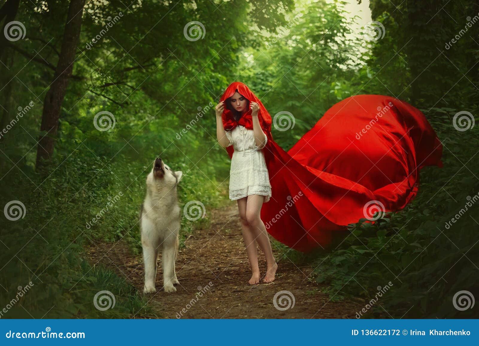 Den sagolika flickan med mörkt hår i kort ljus vit klänning täcker hennes huvud med huven av långt ljust rött fladdra för flyga