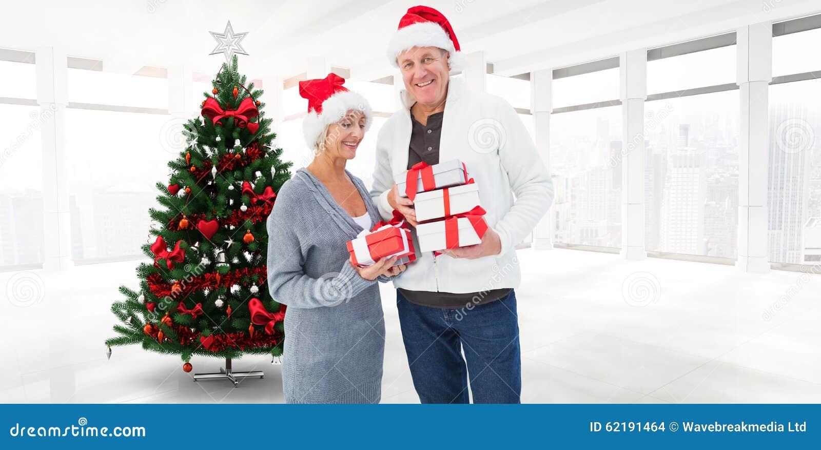 Den sammansatta bilden av festligt mognar hållande julgåvor för par