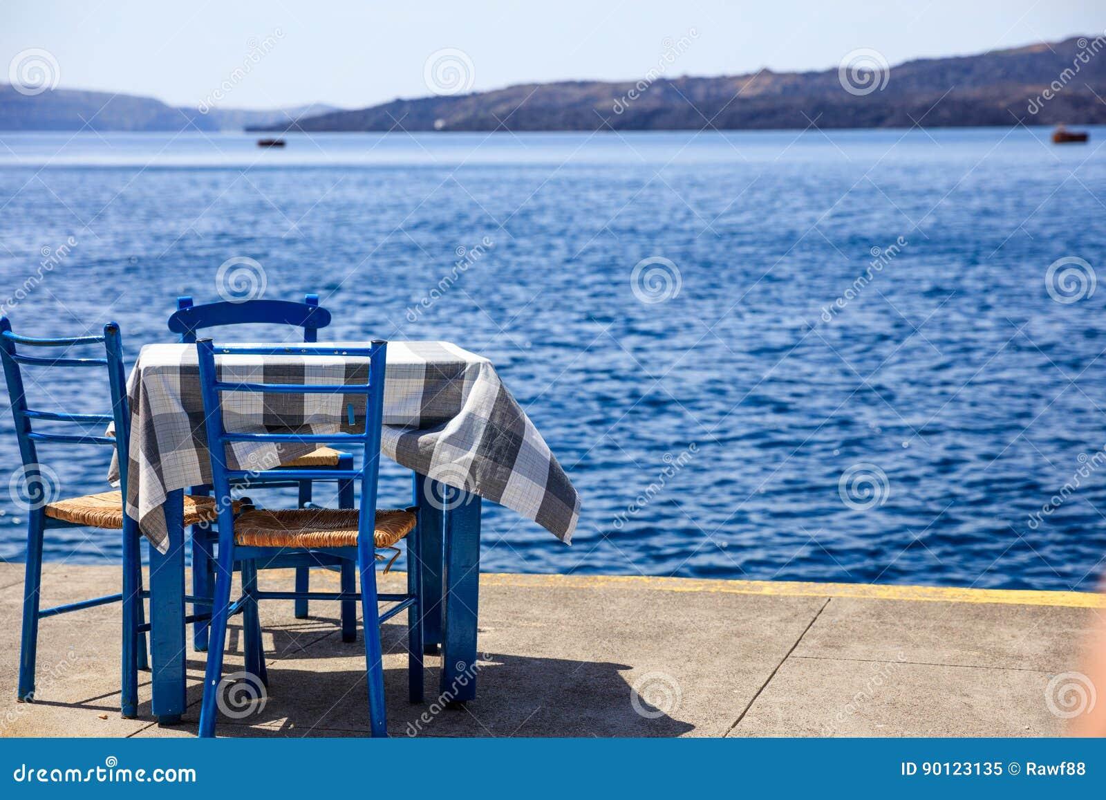 Den Santorini ön, Grekland - bordlägga och stolar på Fira port