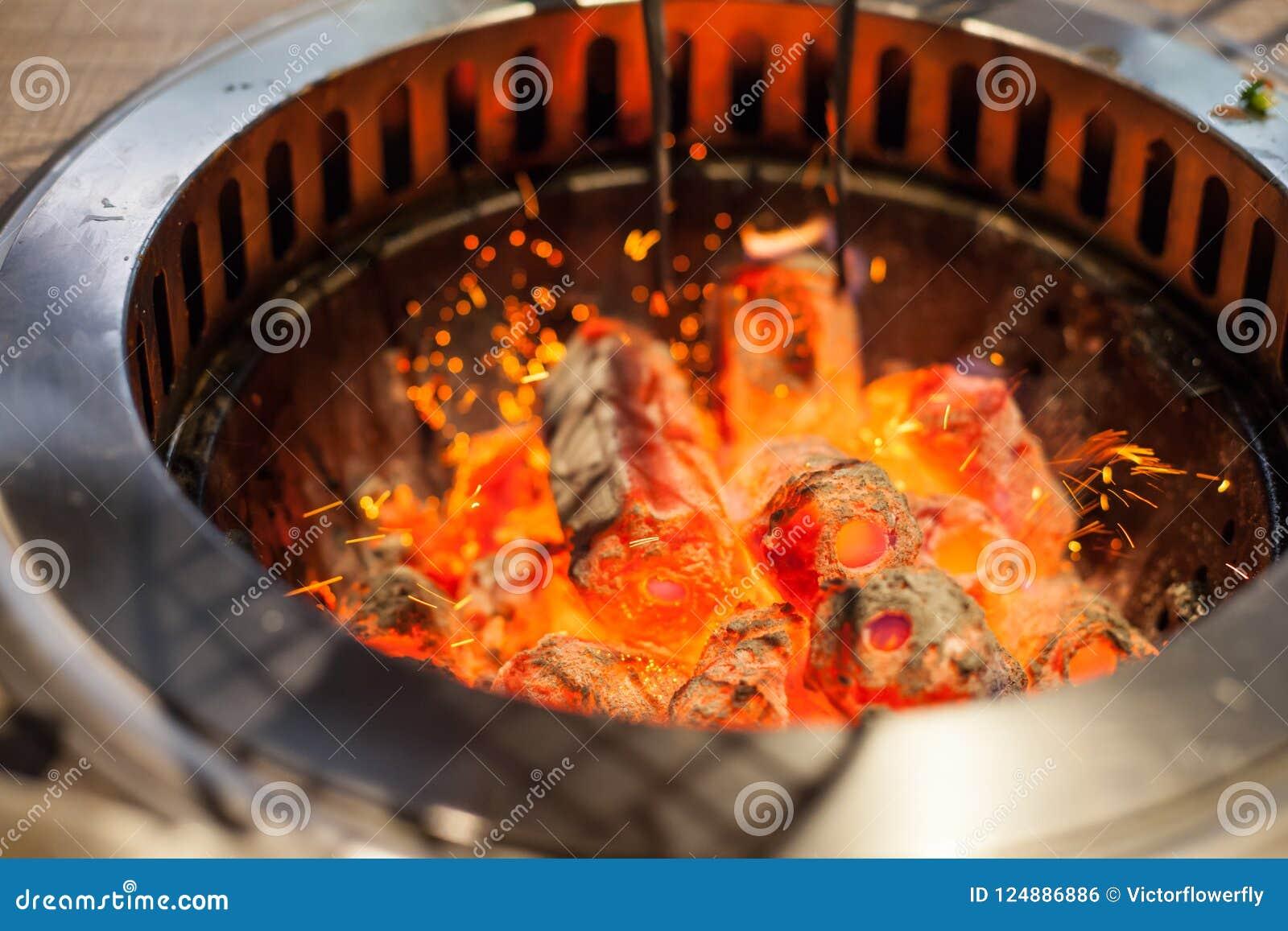 Den selektiva fokusen på att glöda och att flamma varmt naturligt wood kol klumpa sig i bakgrund för ugn för galler för matrestau