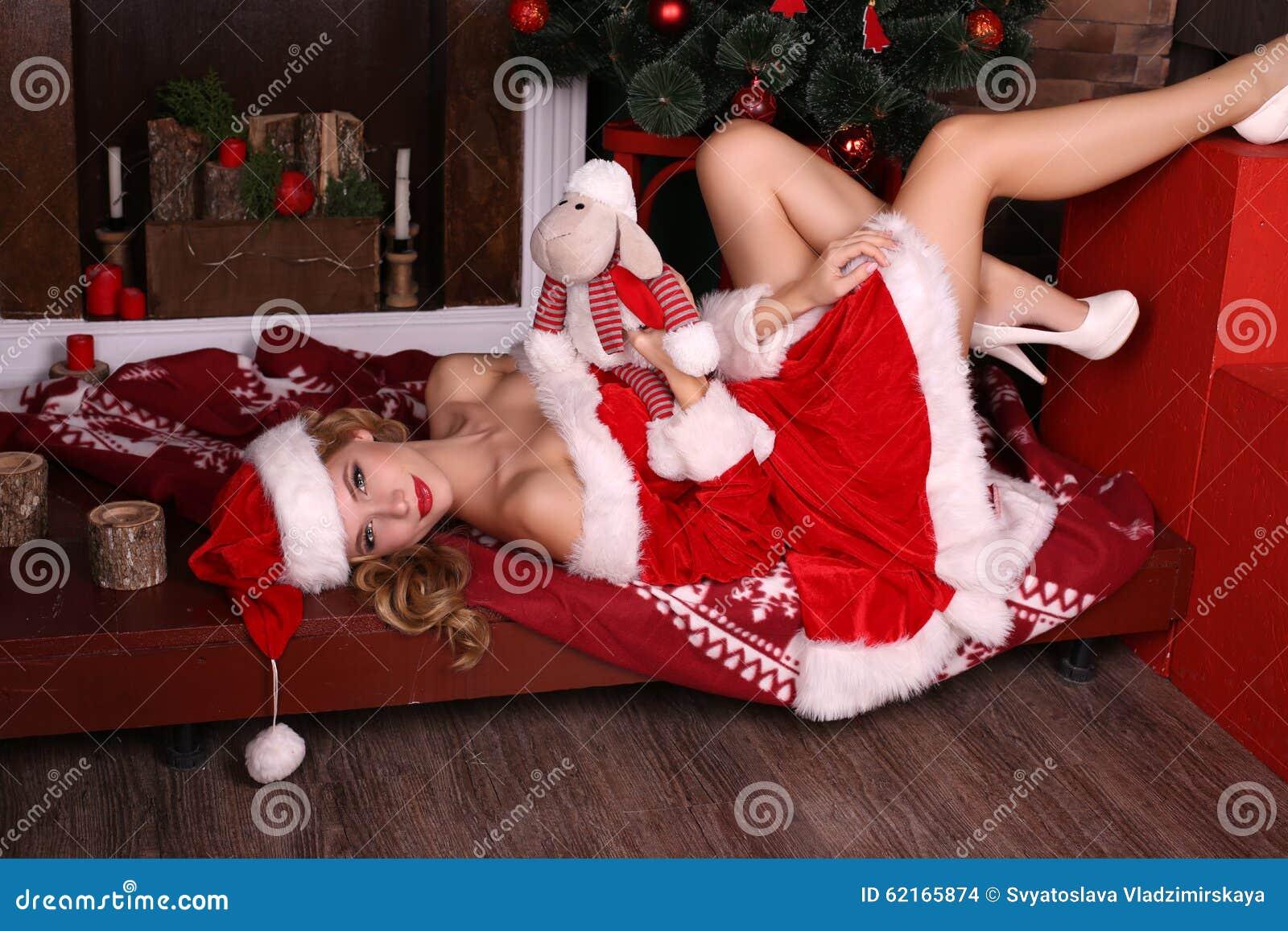 Den sexiga blonda flickan i jultomten kostymerar att posera med julklappar