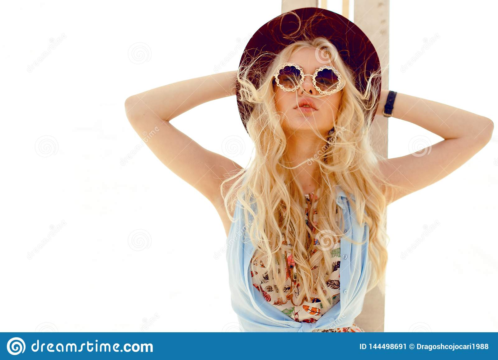 Den sexiga blonda flickan med rund solglasögon, grov bomullstvillskjortan, den gulliga klänningen, våghår och den burgundy hatten