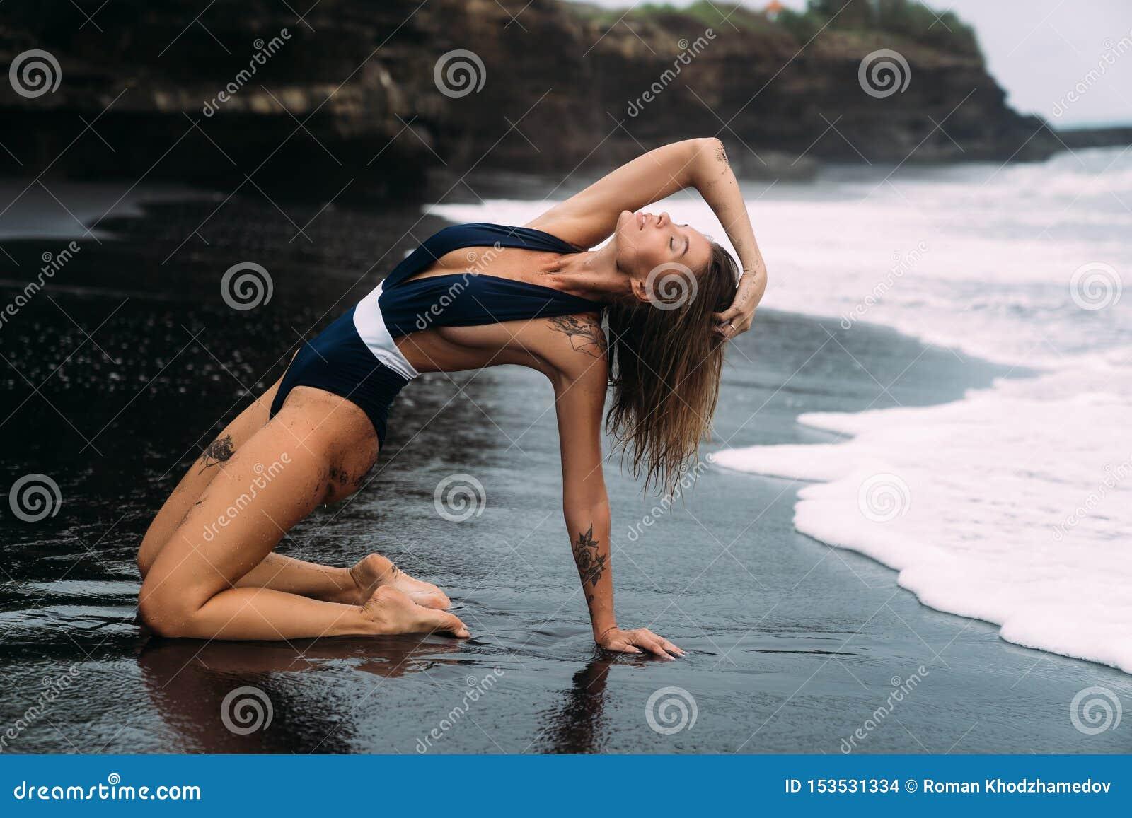 Den sexiga flickan i blå swimwear sitter på stranden med svart sand och stora vågor