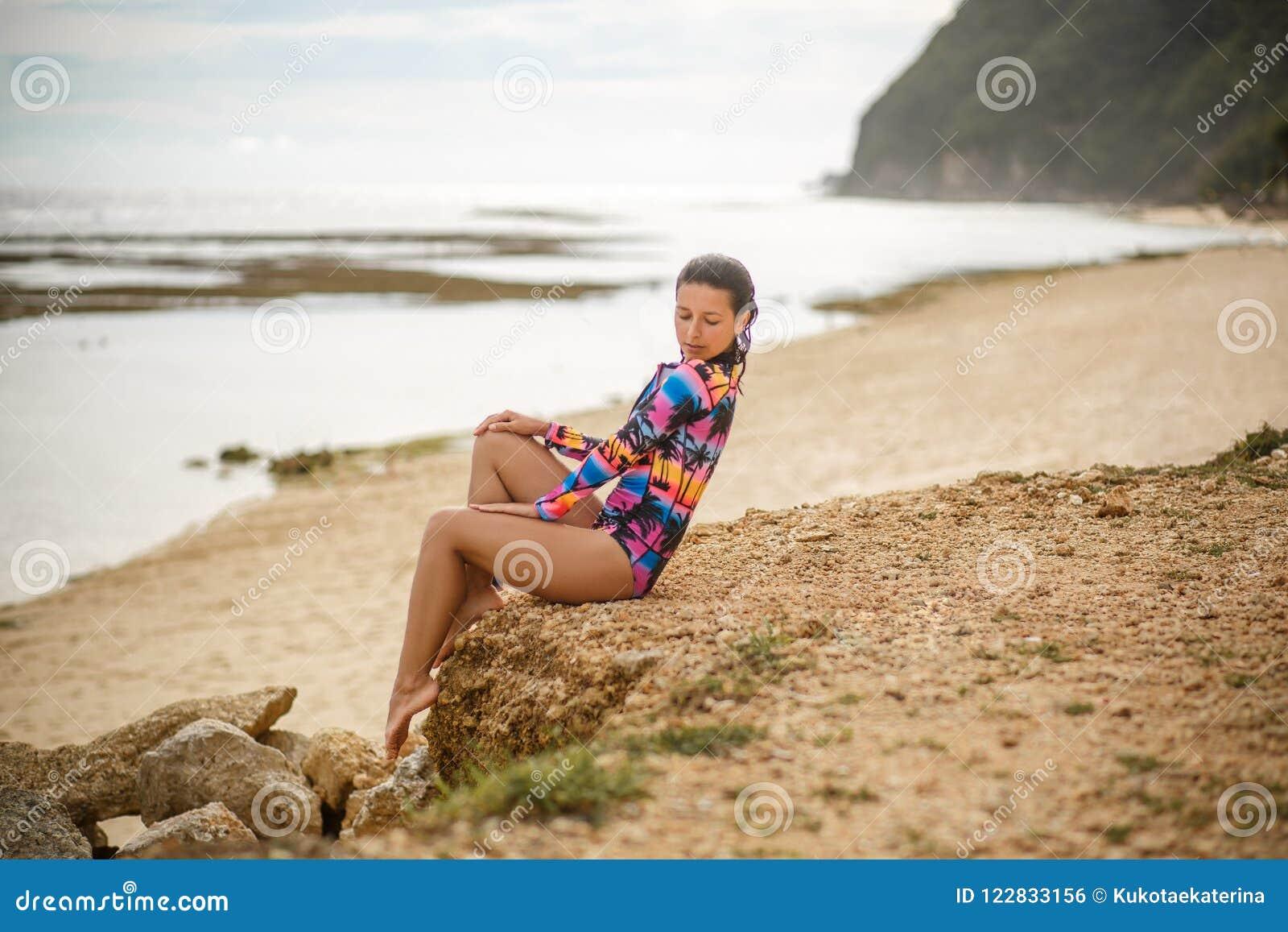 Den sexiga flickan som poserar sammanträde vaggar på, på stranden