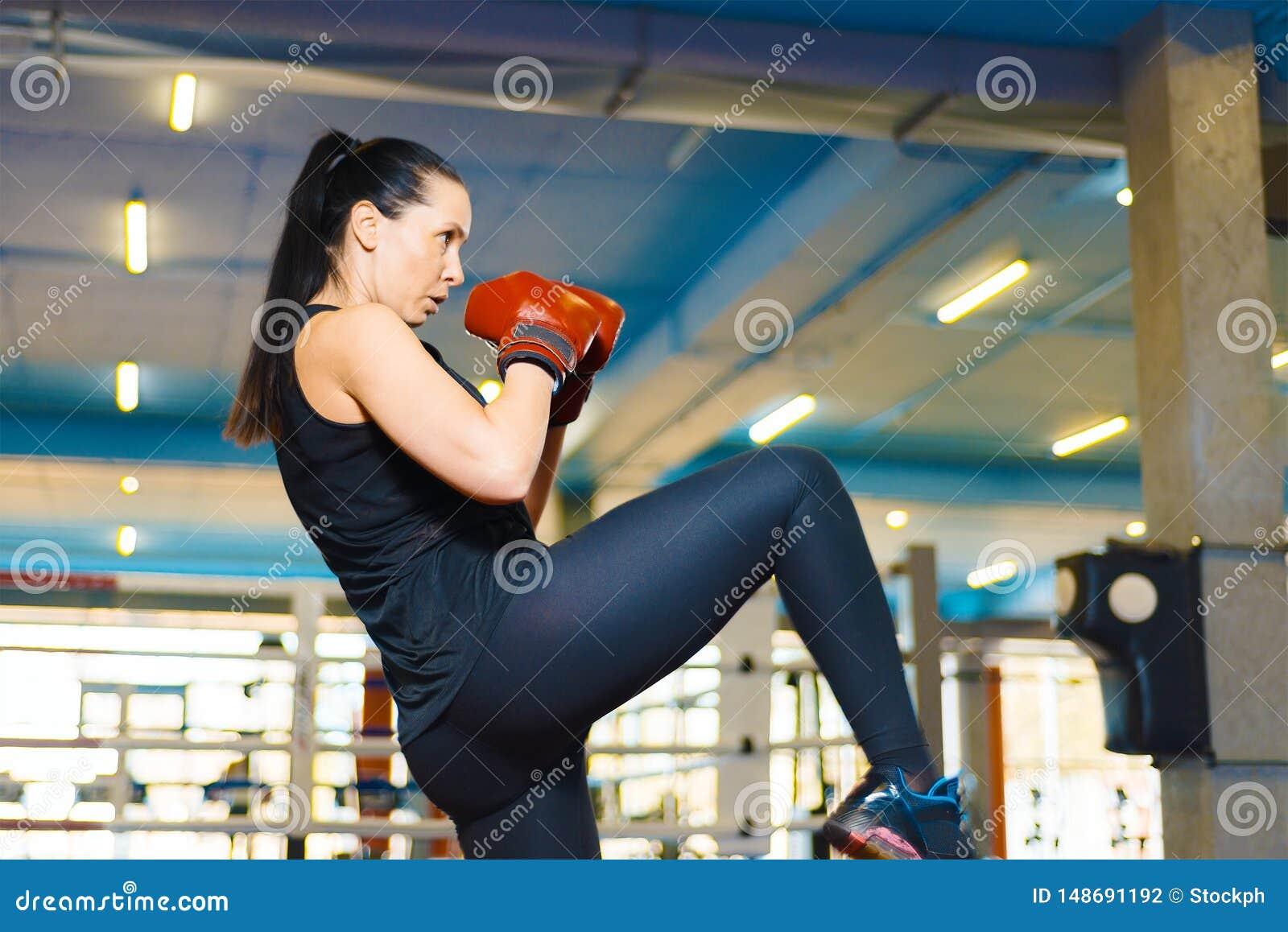 Den sexiga idrotts- flickan g?r en spark in idrottshallen kvinnan i boxninghandskar utbildar kn?et