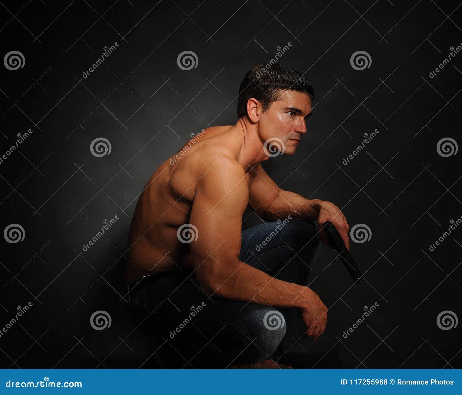 Den sexiga mannen poserar för kameran