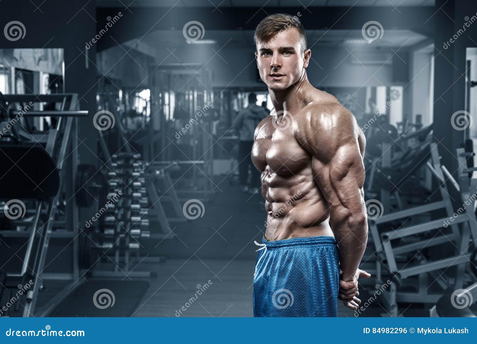Den sexiga muskulösa mannen i idrottshallen, format buk- som visar tränga sig in Manlig naken torsoabs för kroppsbyggare som utar