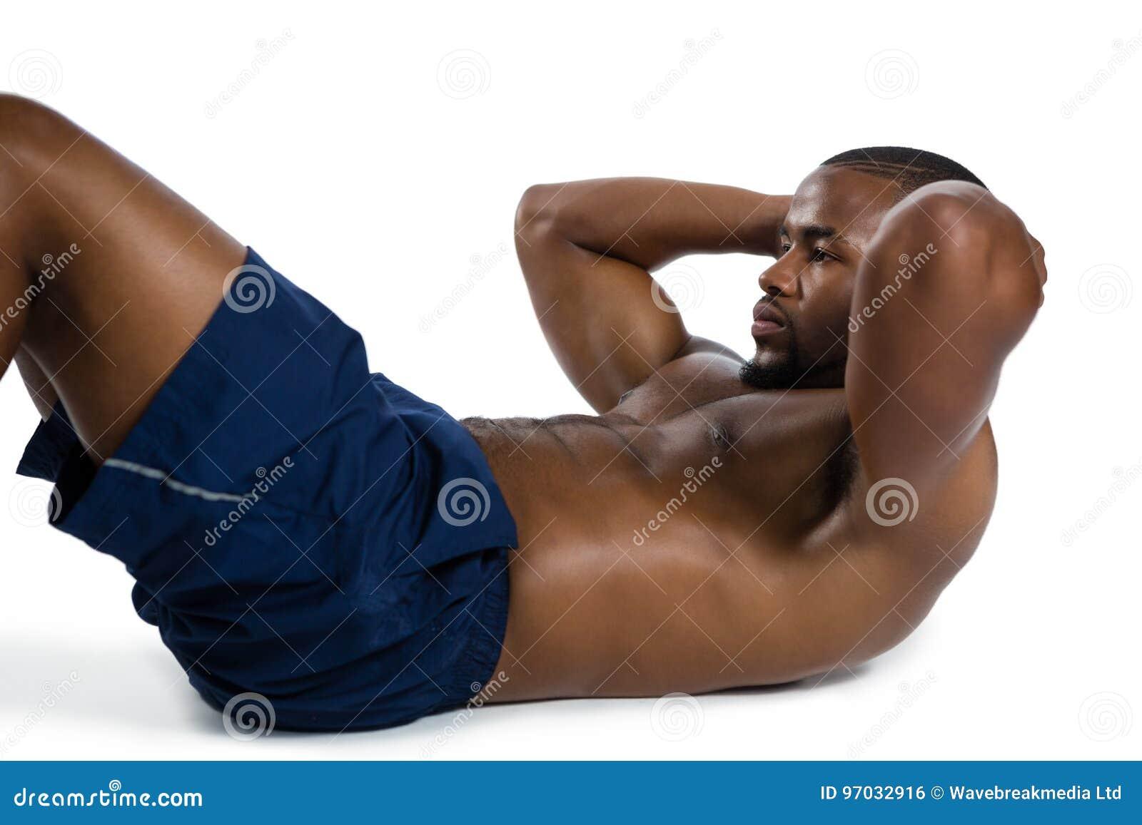 Den Shirtless manliga idrottsman nen som övning sitter, ups