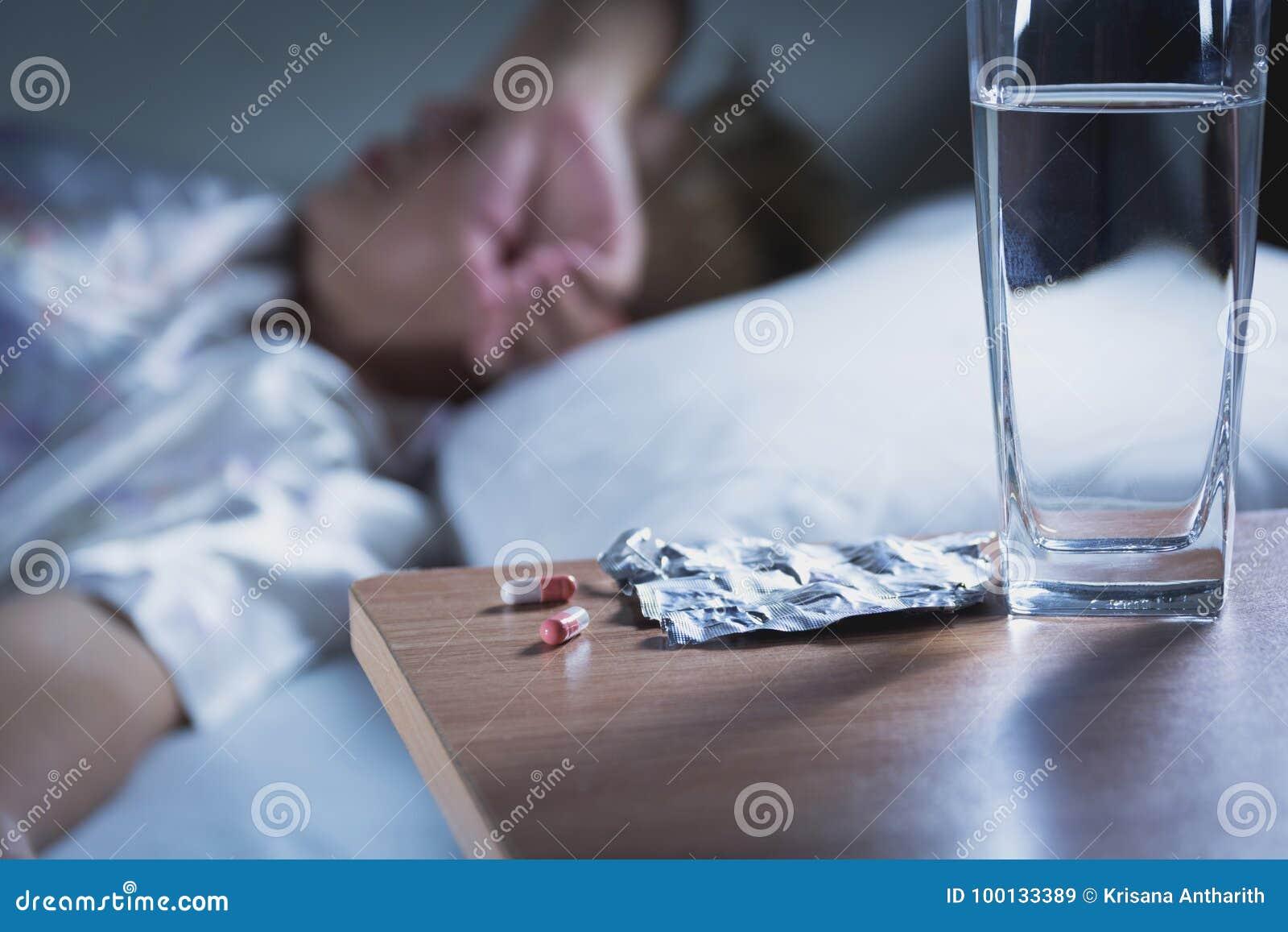 Den sjuka kvinnan tar kapselpreventivpilleren och drinkvatten, innan han sover