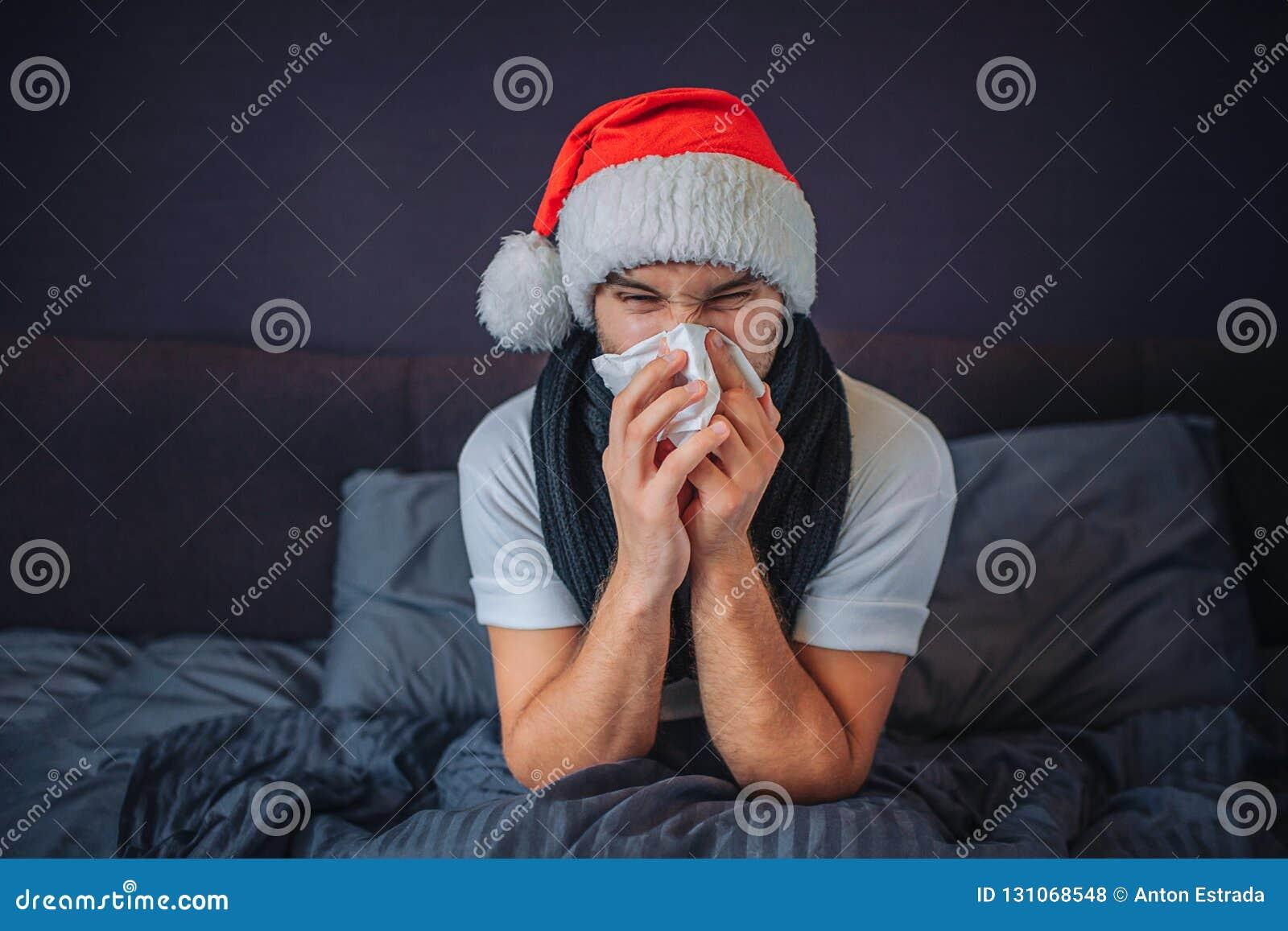 Den sjuka unga mannen i röd hatt för jul sitter på säng Han täckas med filten Grabb som nyser in i silkespapper Han lider Barn