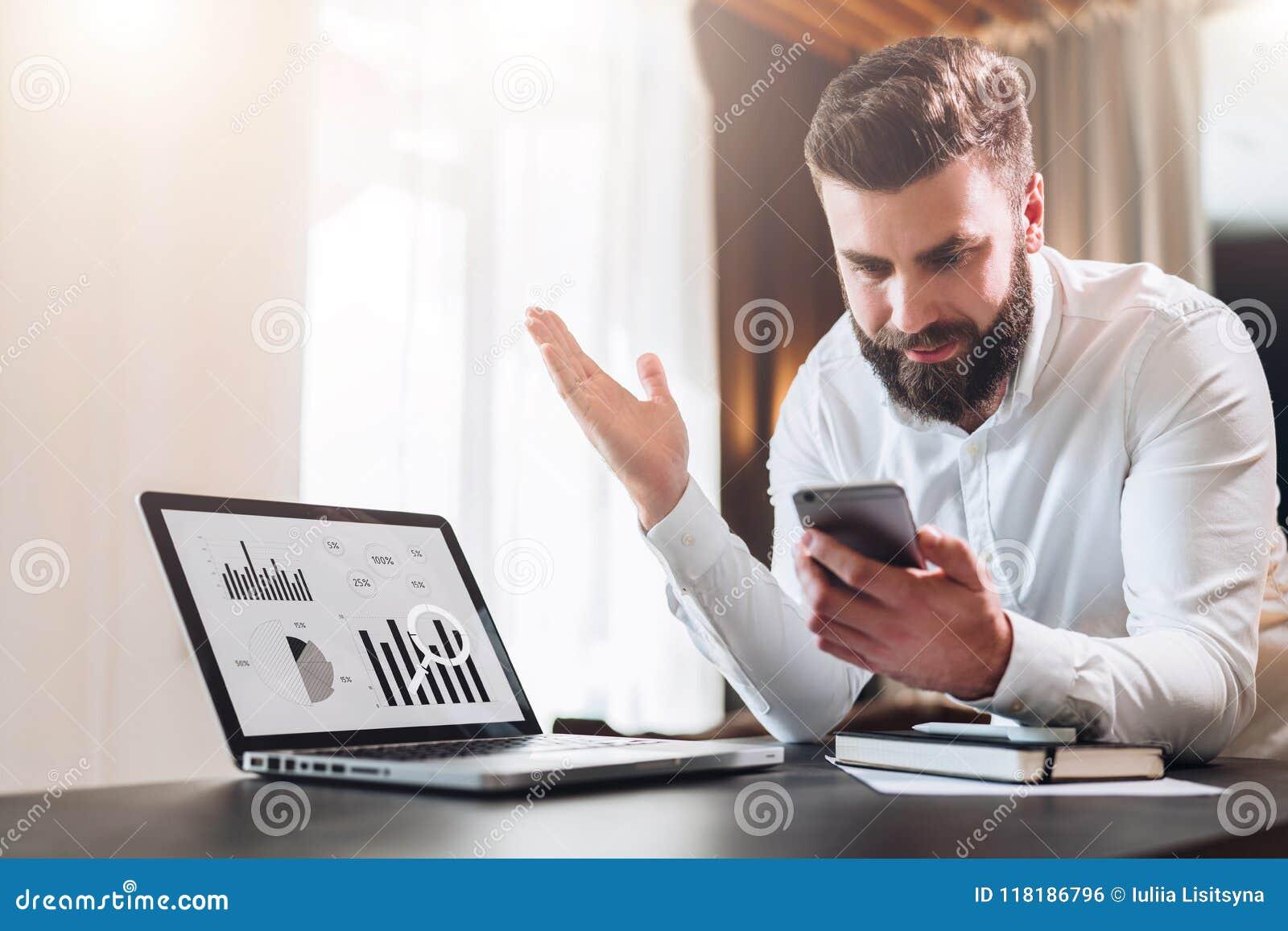 Den skäggiga affärsmannen i den vita skjortan sitter på tabellen framme av bärbara datorn med grafer, diagram, diagram på skärmen