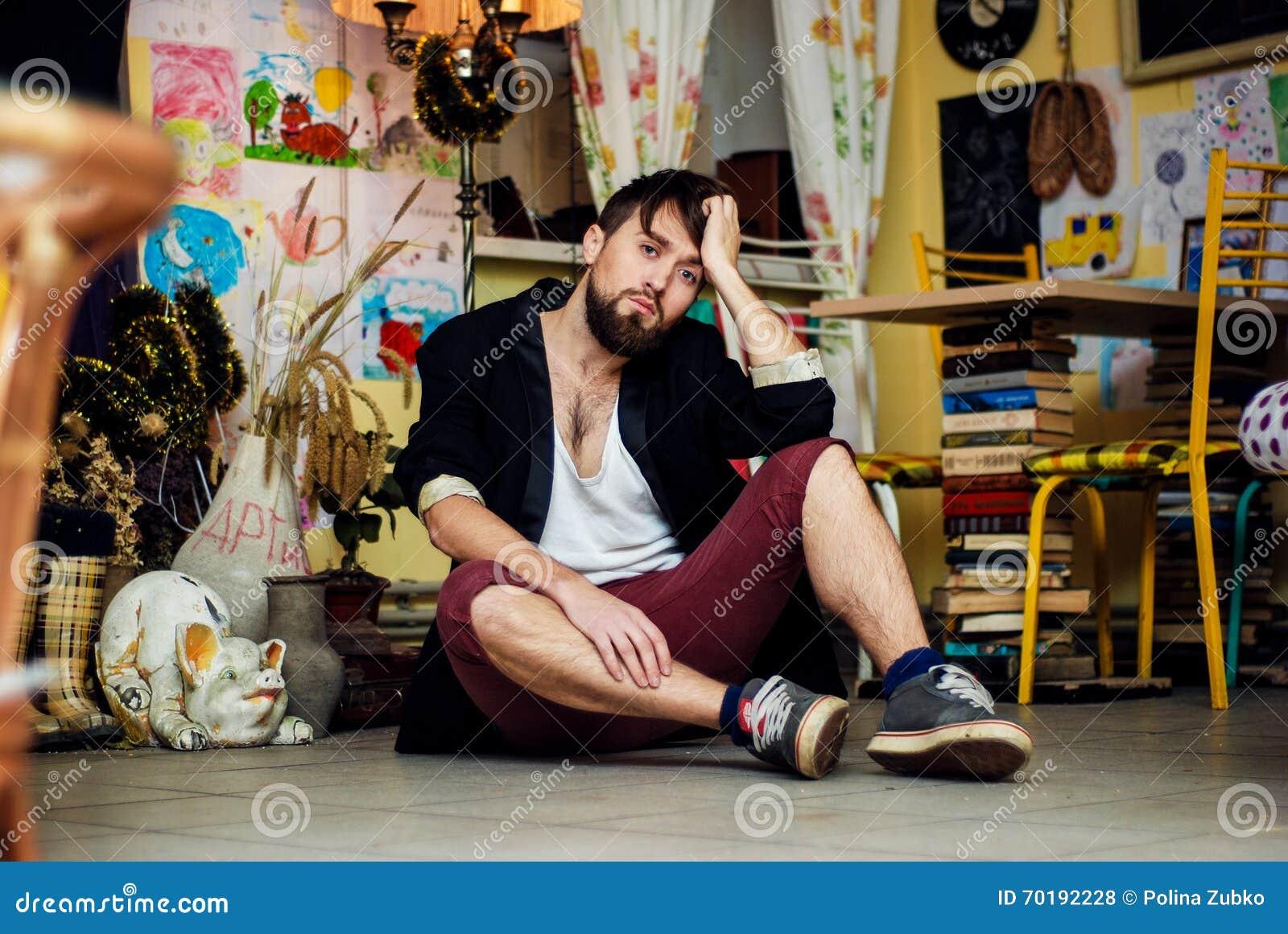Den skäggiga grabben sitter på golvet