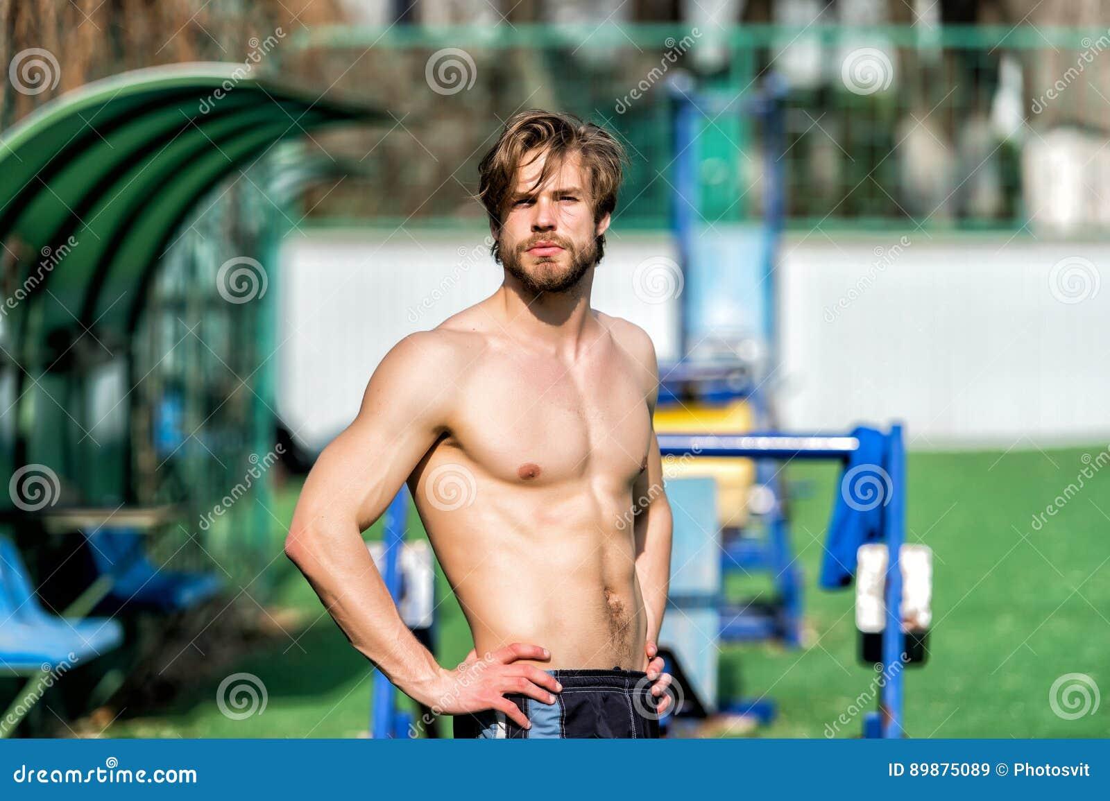 Den skäggiga mannen har stilfullt hår, den idrotts- kroppen kopplar av på stadion